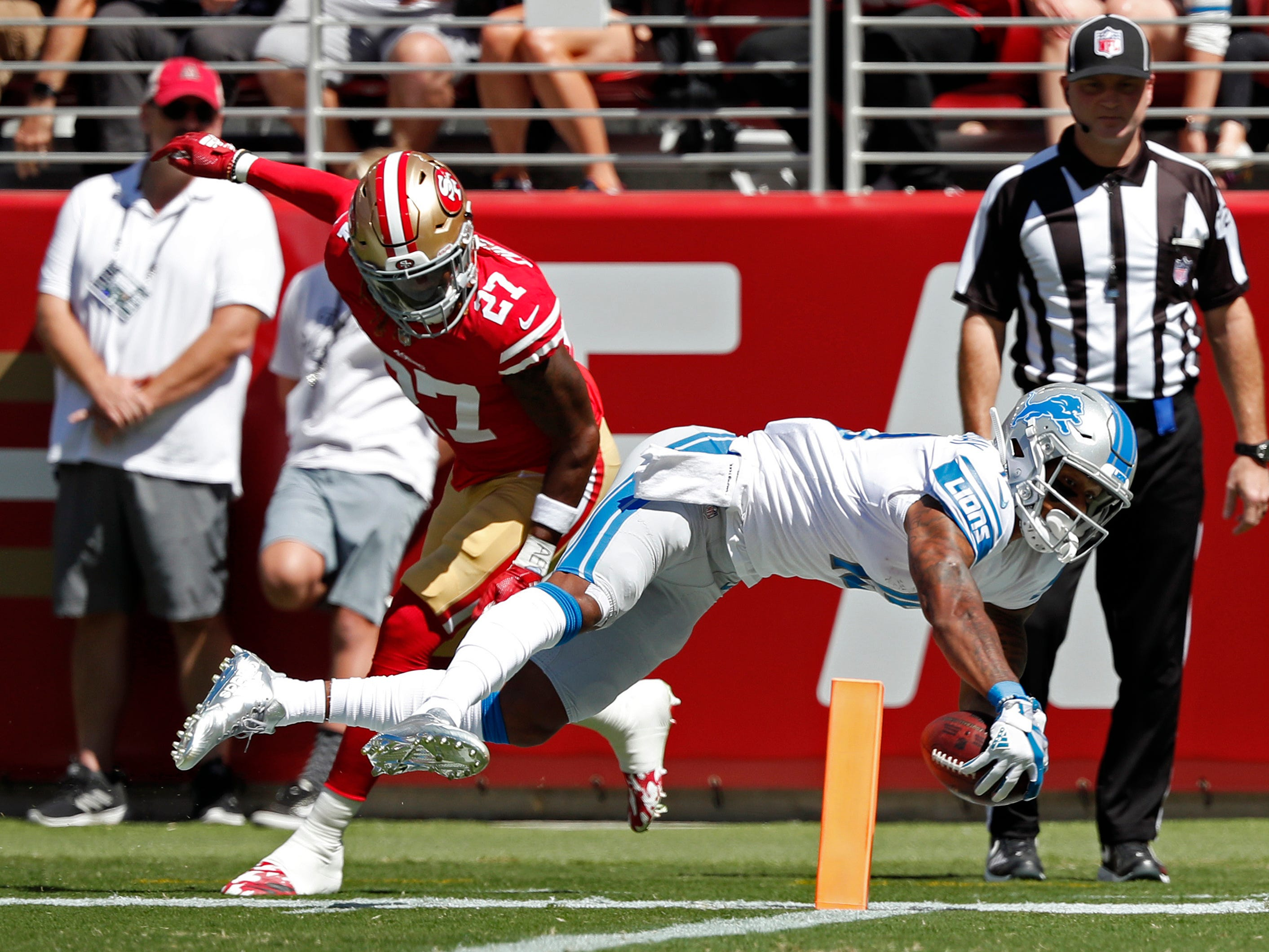 Detroit Lions wide receiver Kenny Golladay, front right, scores a touchdown as San Francisco 49ers defensive back Adrian Colbert (27) looks on during the first half.
