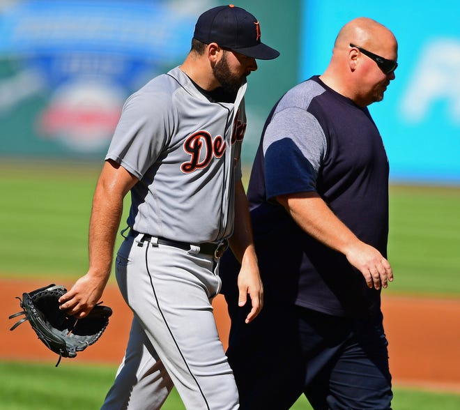 Detroit Tigers starting pitcher Michael Fulmer walks to the dugout with trainer Doug Teter on Saturday.