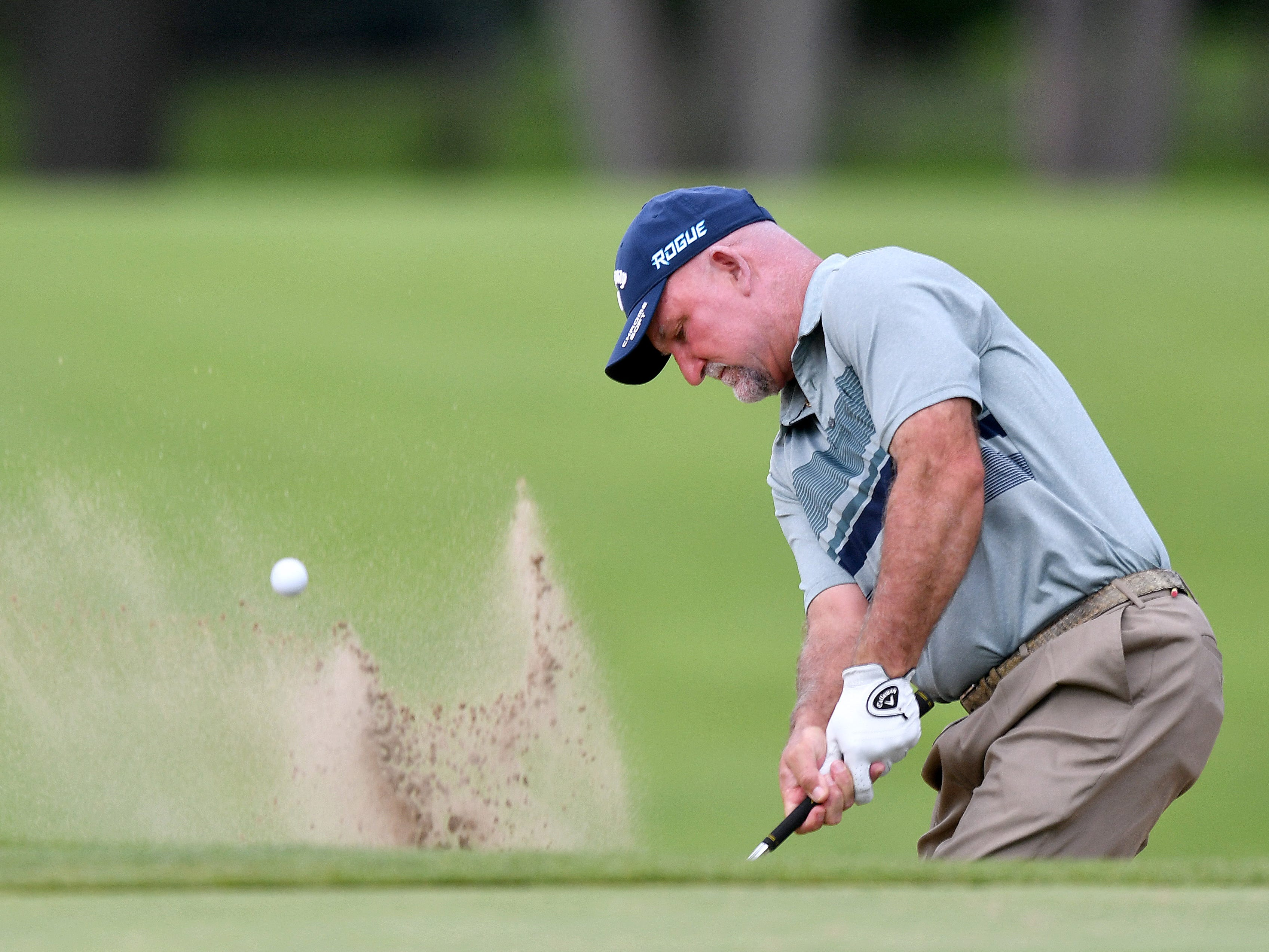 Marco Dawson hits out of a bunker on the first hole at the Ally Challenge.
