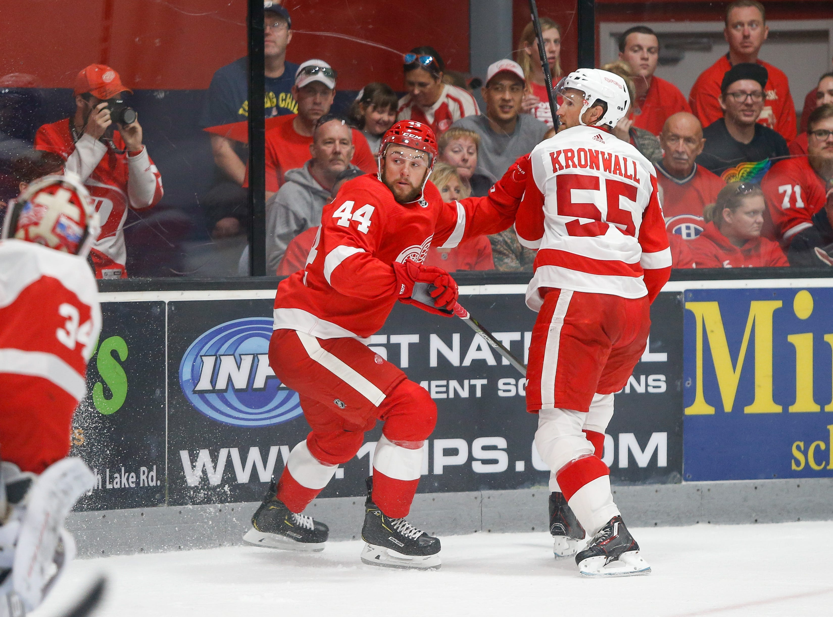 Dylan Sadowy and Niklas Kronwall look try to locate a high bouncing puck after knocking it into the boards.
