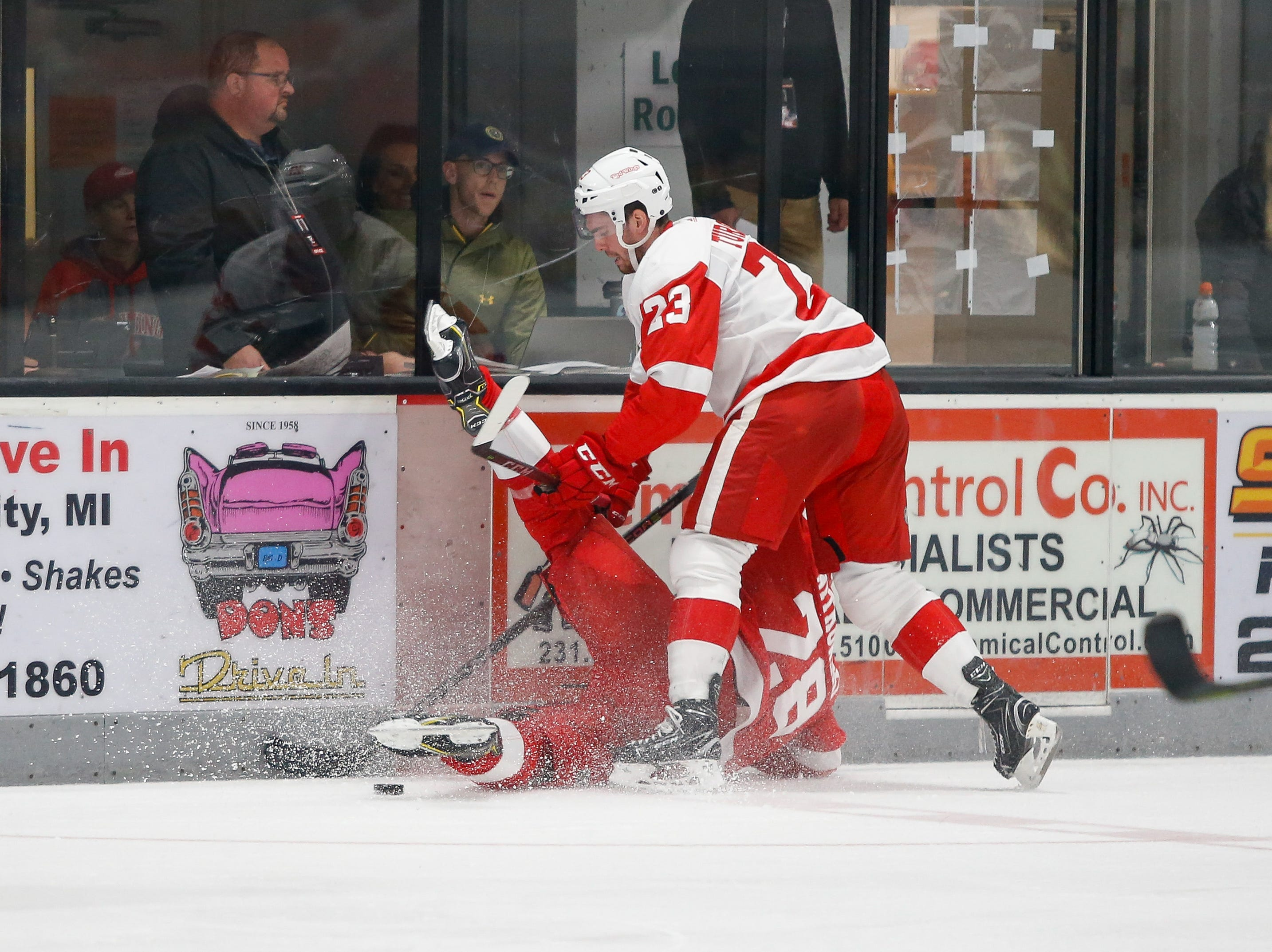 Luke Witkowski is upended along the boards in a puck battle with Dominic Turgeon (23).