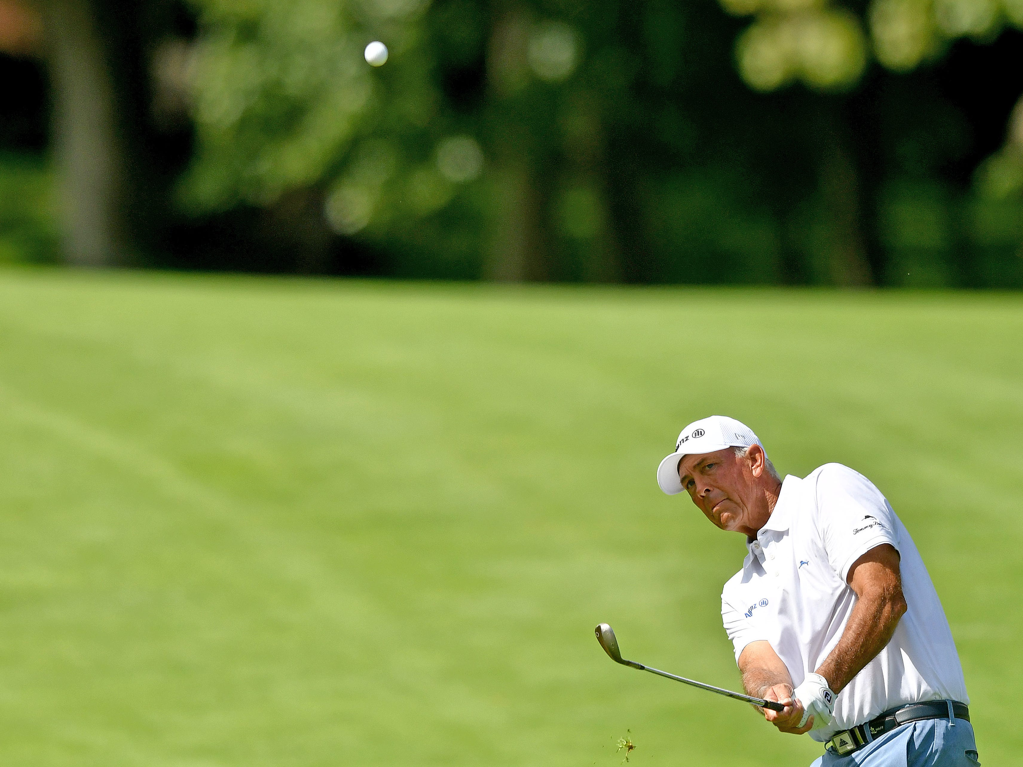 Tom Lehman watches his approach shot on the first hole.