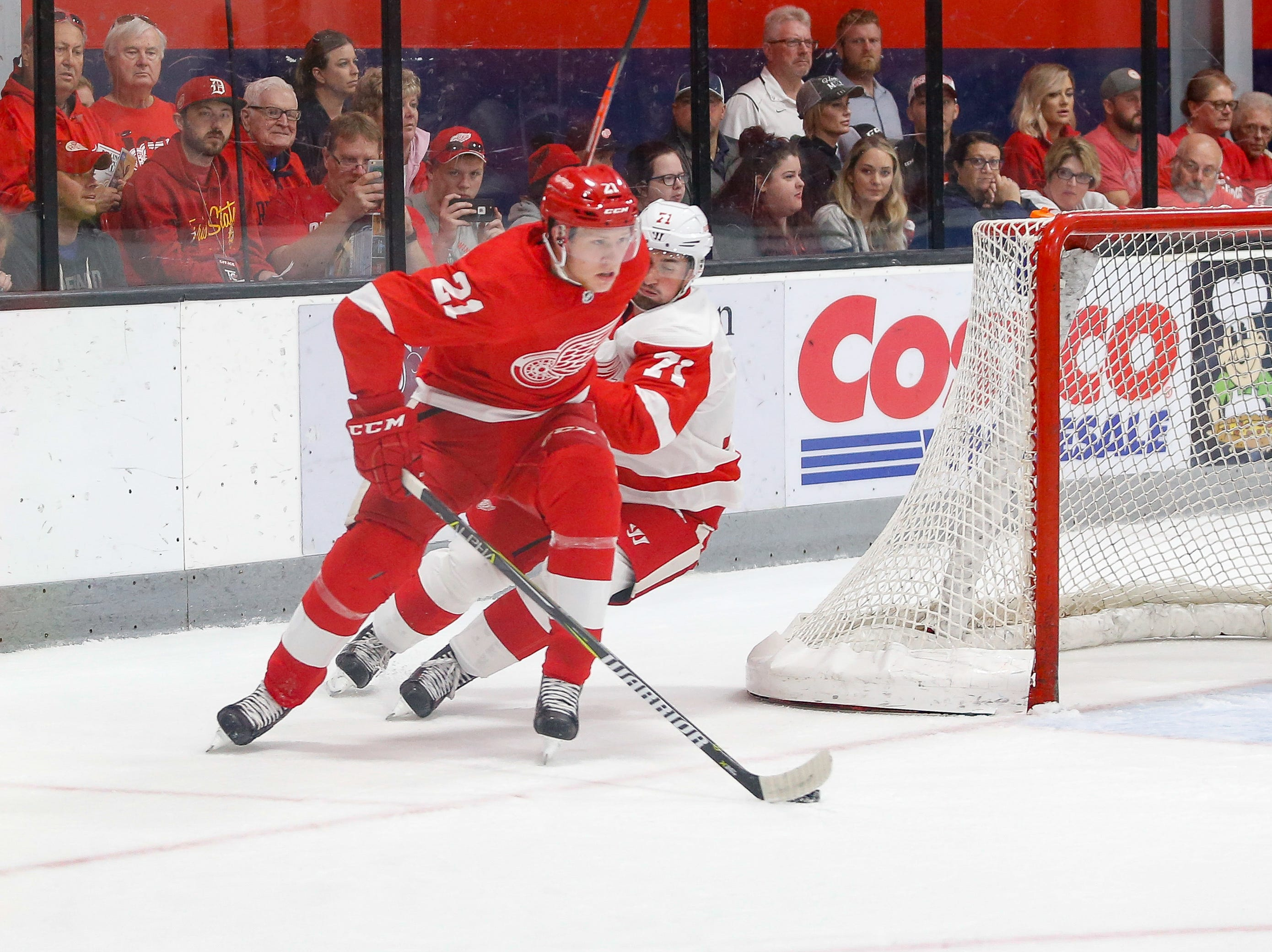 Dennis Cholowski (21) tries to escape his own zone with the puck as Dylan Larkin (71) pesters.