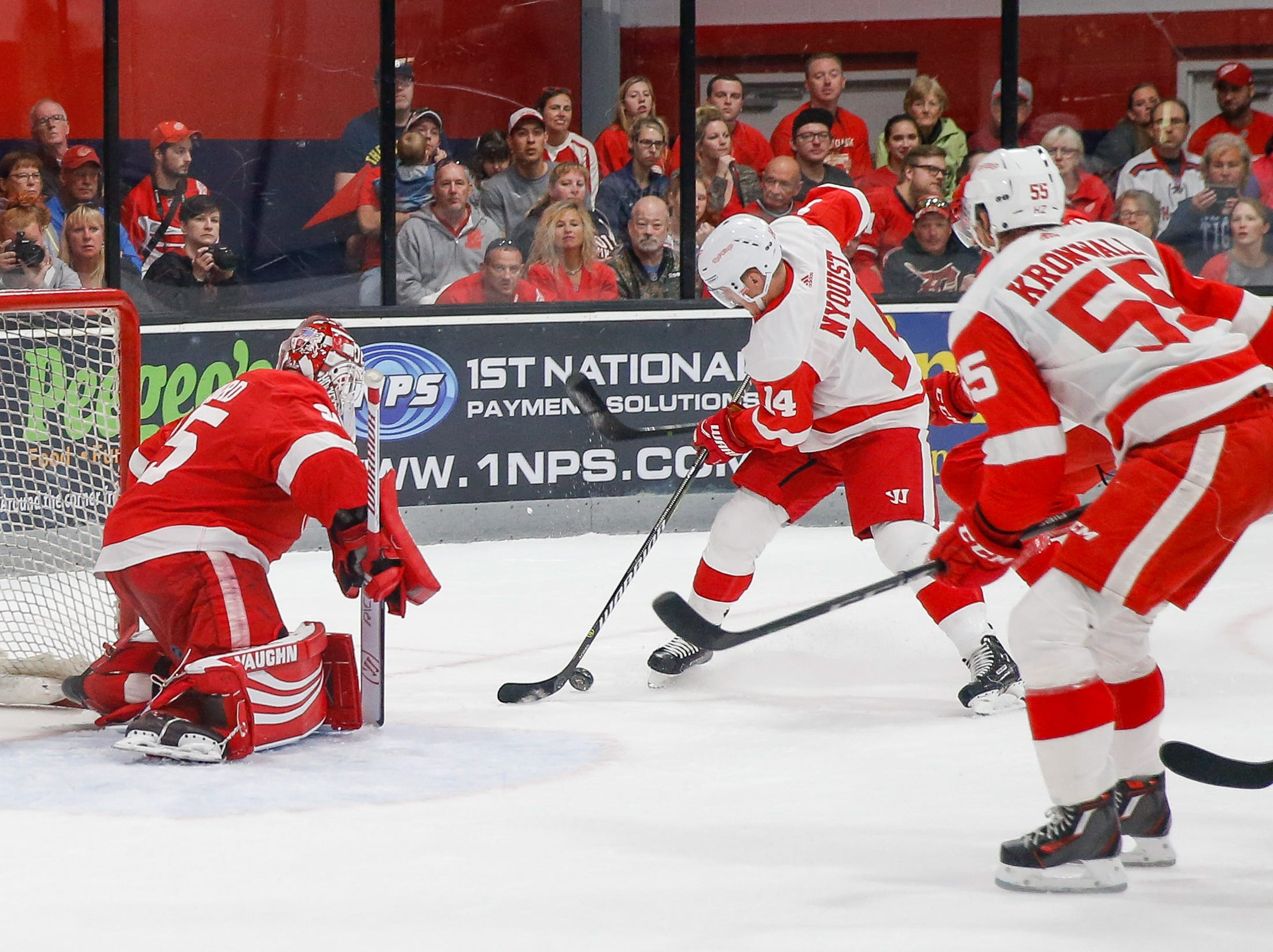 Gustav Nyquist battles defenders in an attempt to slip the puck past Team Red goaltender Jimmy Howard. He was not successful.