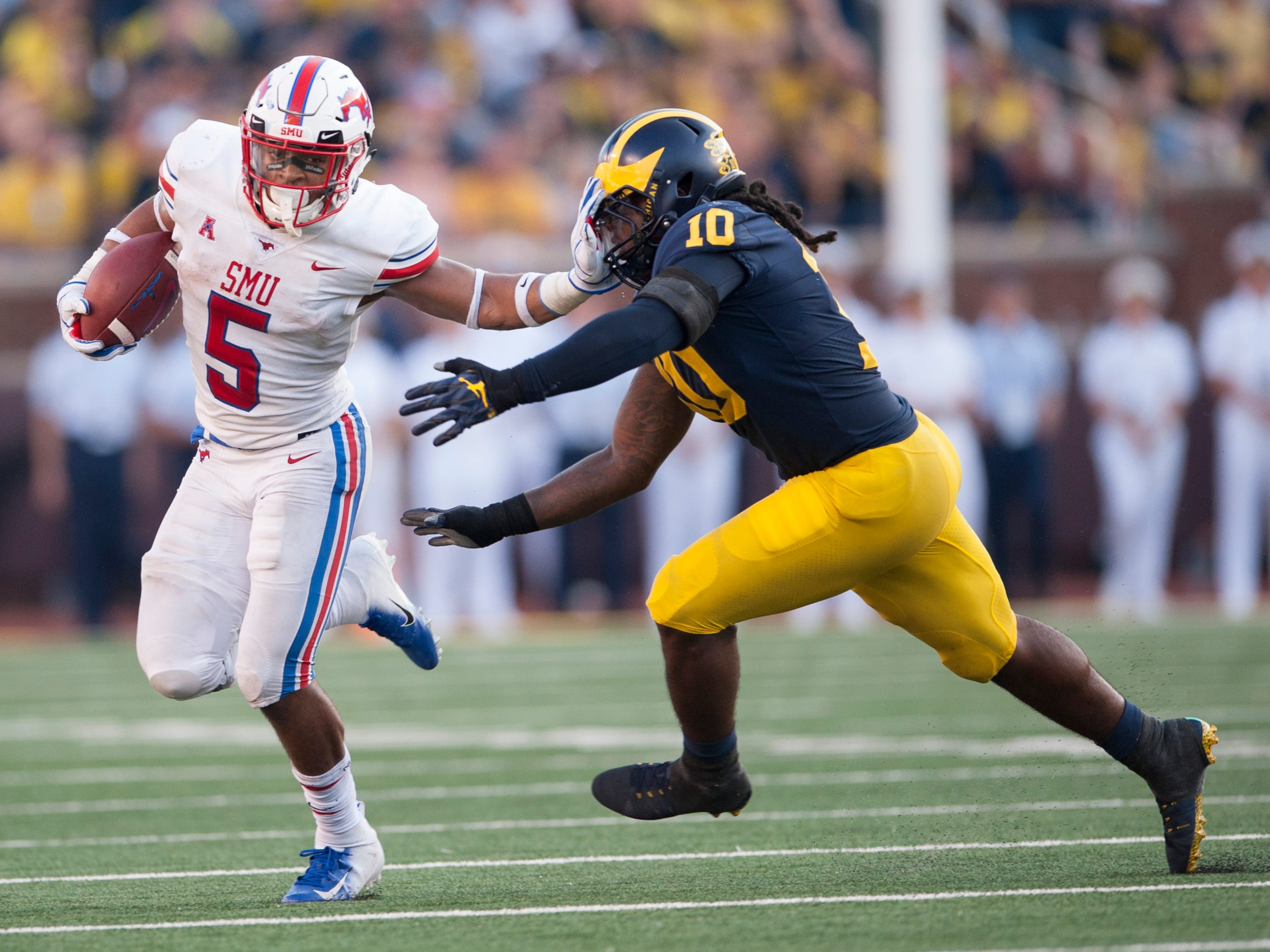 Southern Methodist running back Xavier Jones stiff arms Michigan linebacker Devin Bush on this second half run.