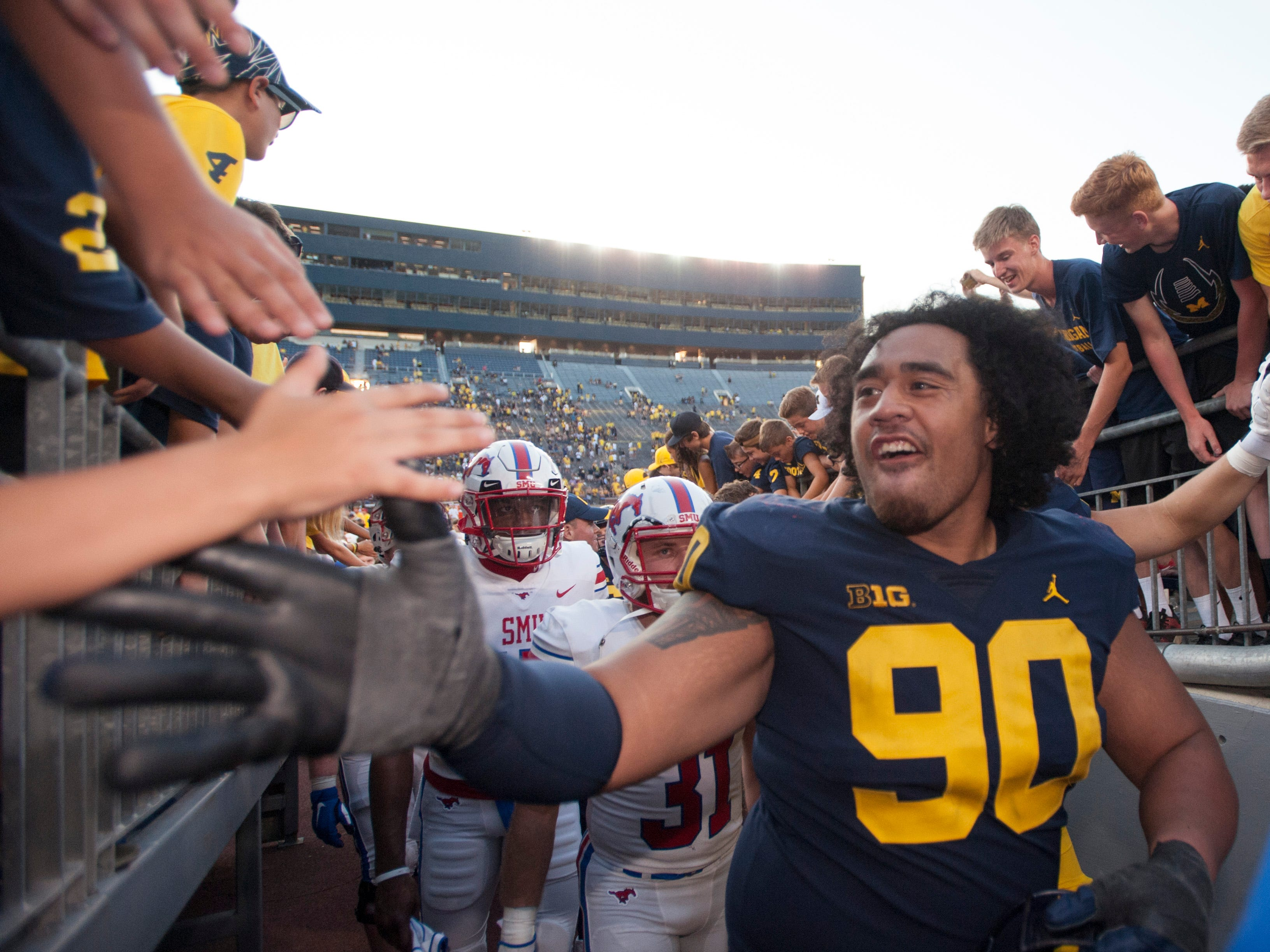 Michigan defensive lineman Bryan Mone high fives fans as they head up the Michigan Stadium tunnel after the game.
