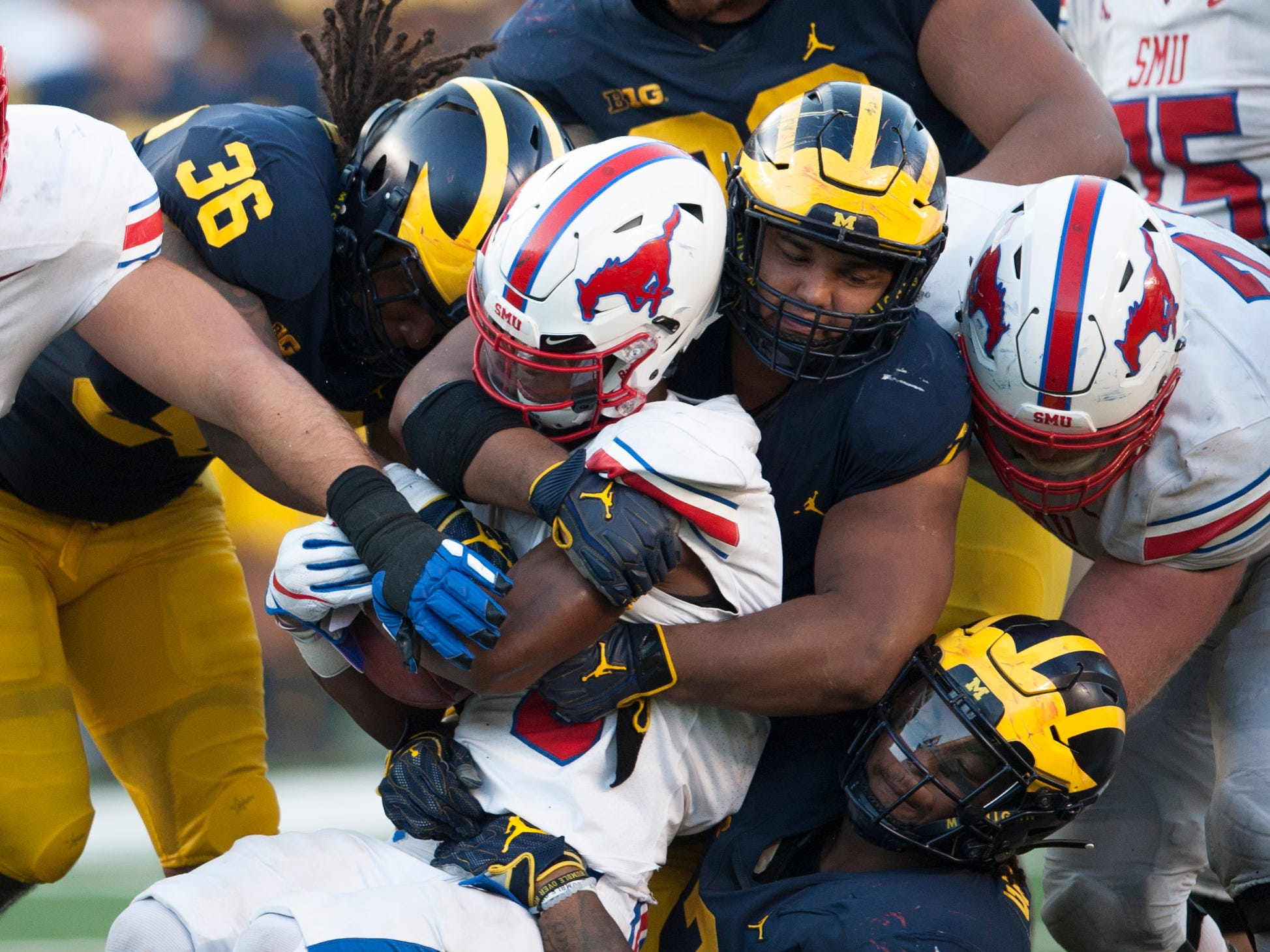 Michigan defenders gang tackle Southern Methodist running back Xavier Jones in the second half.