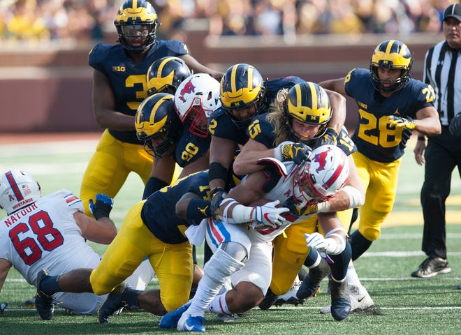 Michigan defensive lineman Chase Winovich (15) and a host of other Michigan defenders gang tackle SMU running back Xavier Jones for a loss in the second quarter on Saturday.