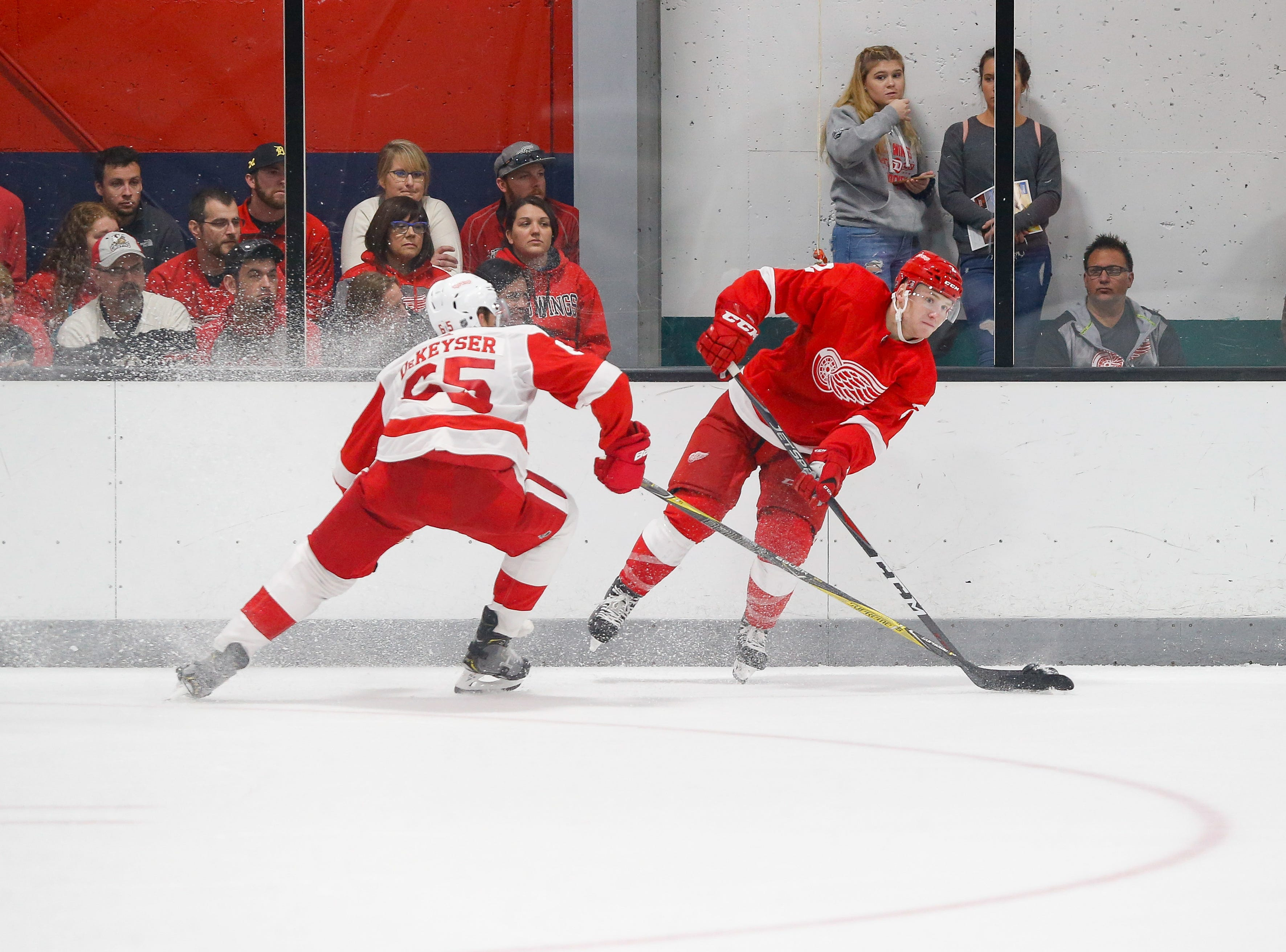 Danny DeKeyser tries to poke the puck off the stick of Red defenseman Joe Hicketts.