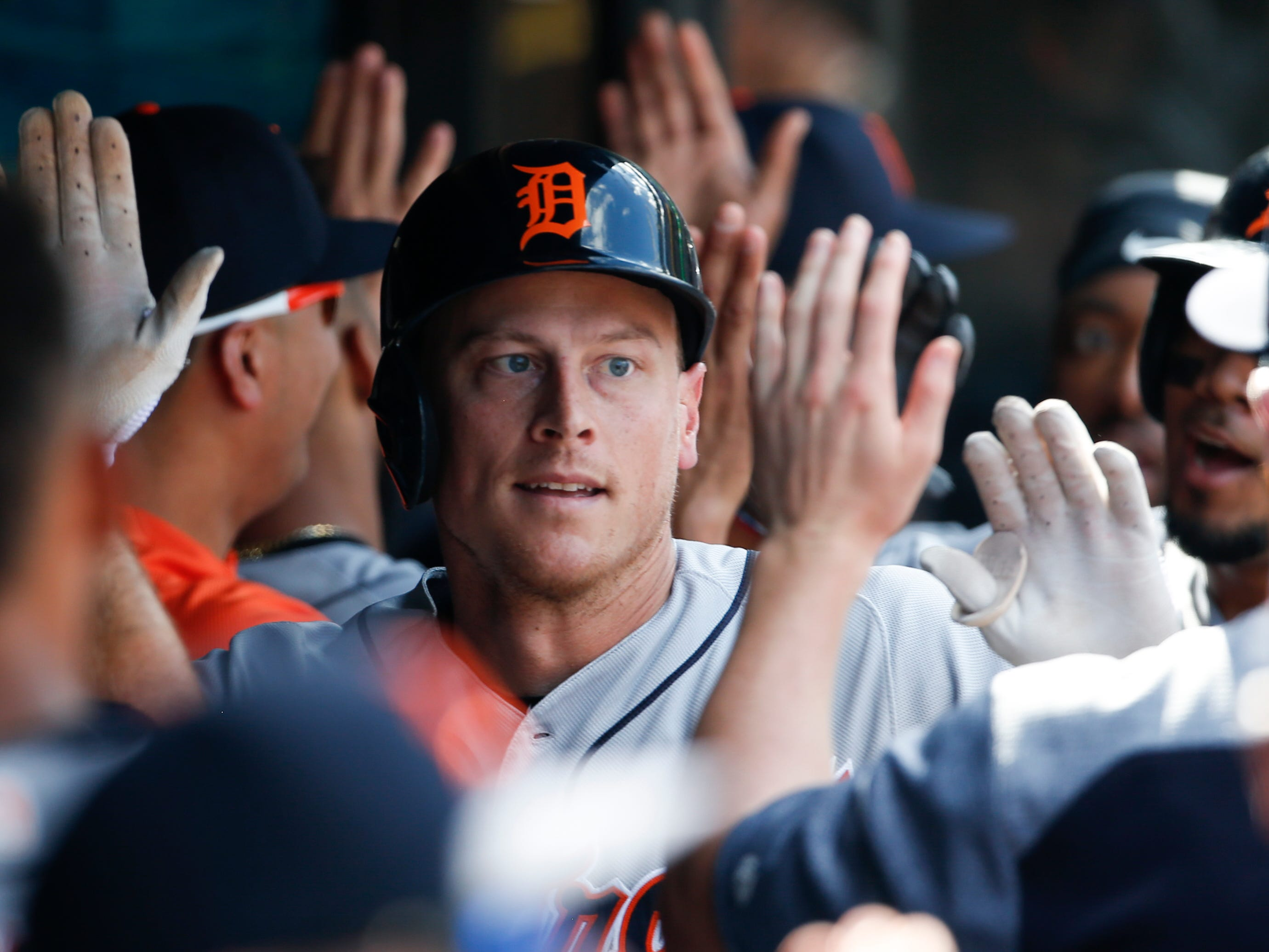 Detroit Tigers' Jim Adduci celebrates in the dugout with teammates after hitting a three run home run off Cleveland Indians' Shane Bieber during the fifth inning.