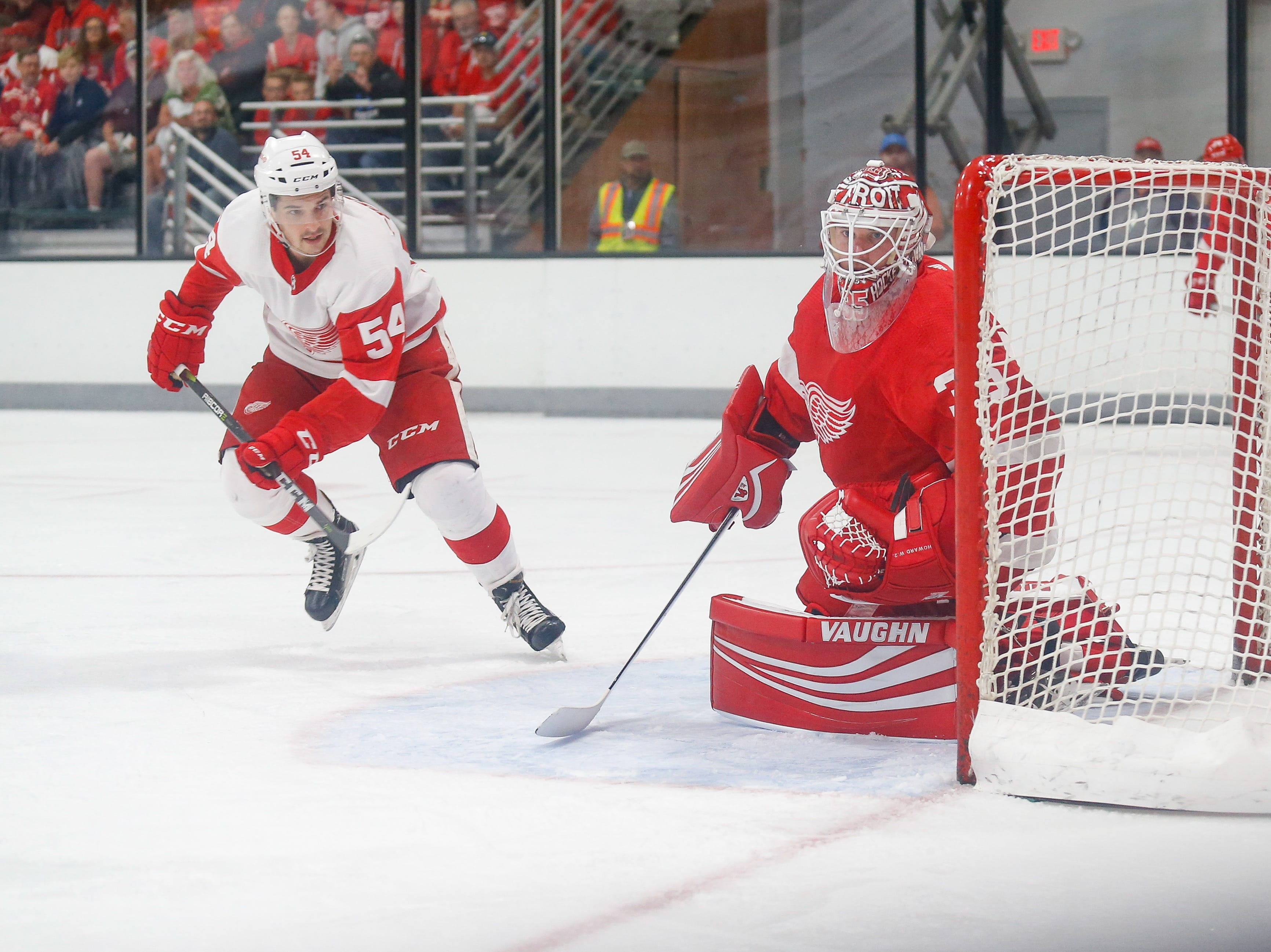 Matt Puempel races for the corner as goaltender Jimmy Howard watches the action there.