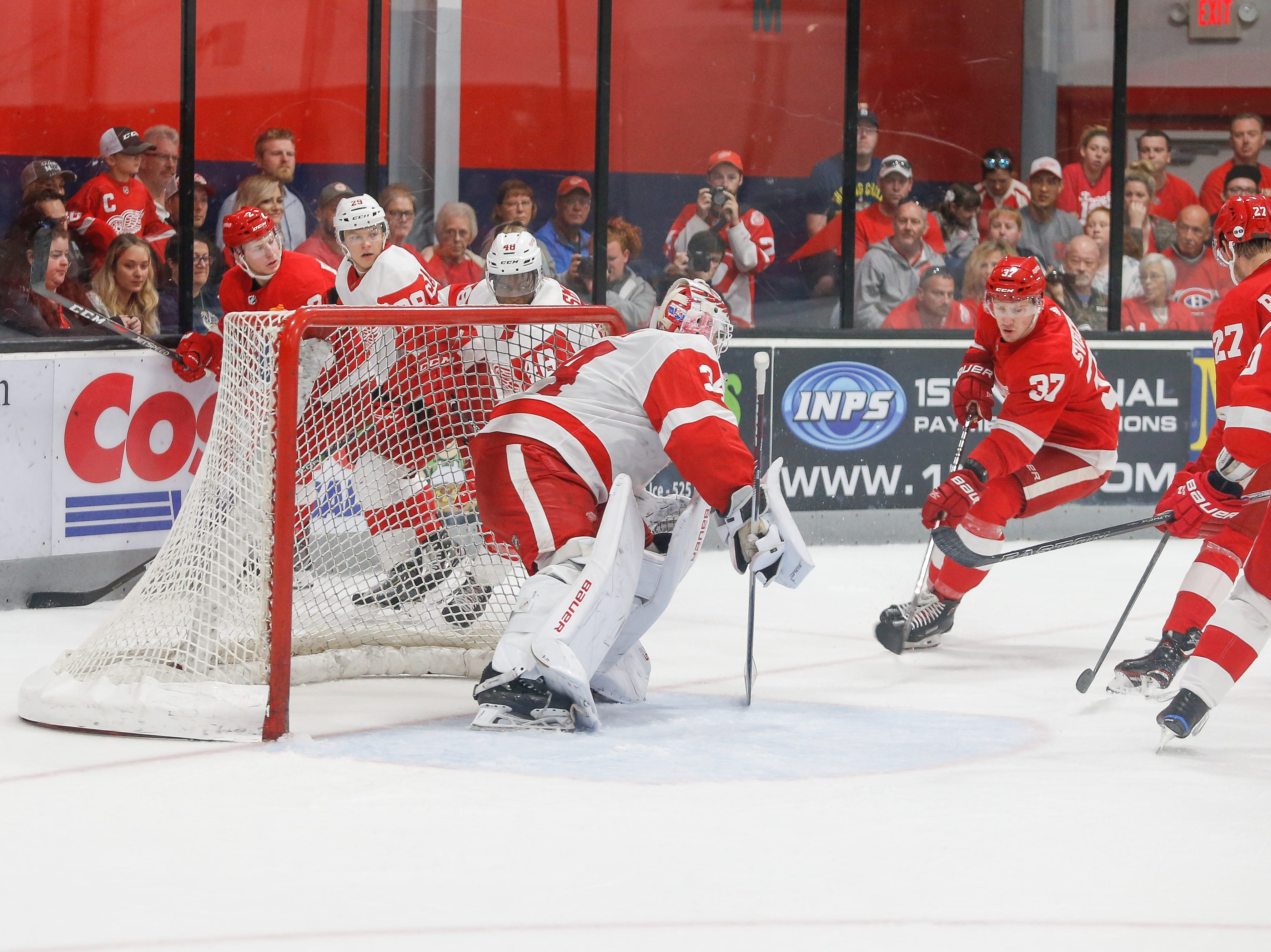 Evgeny Svechnikov moves in on goaltender Patrik Rybar as other Wings, red and white, watch.