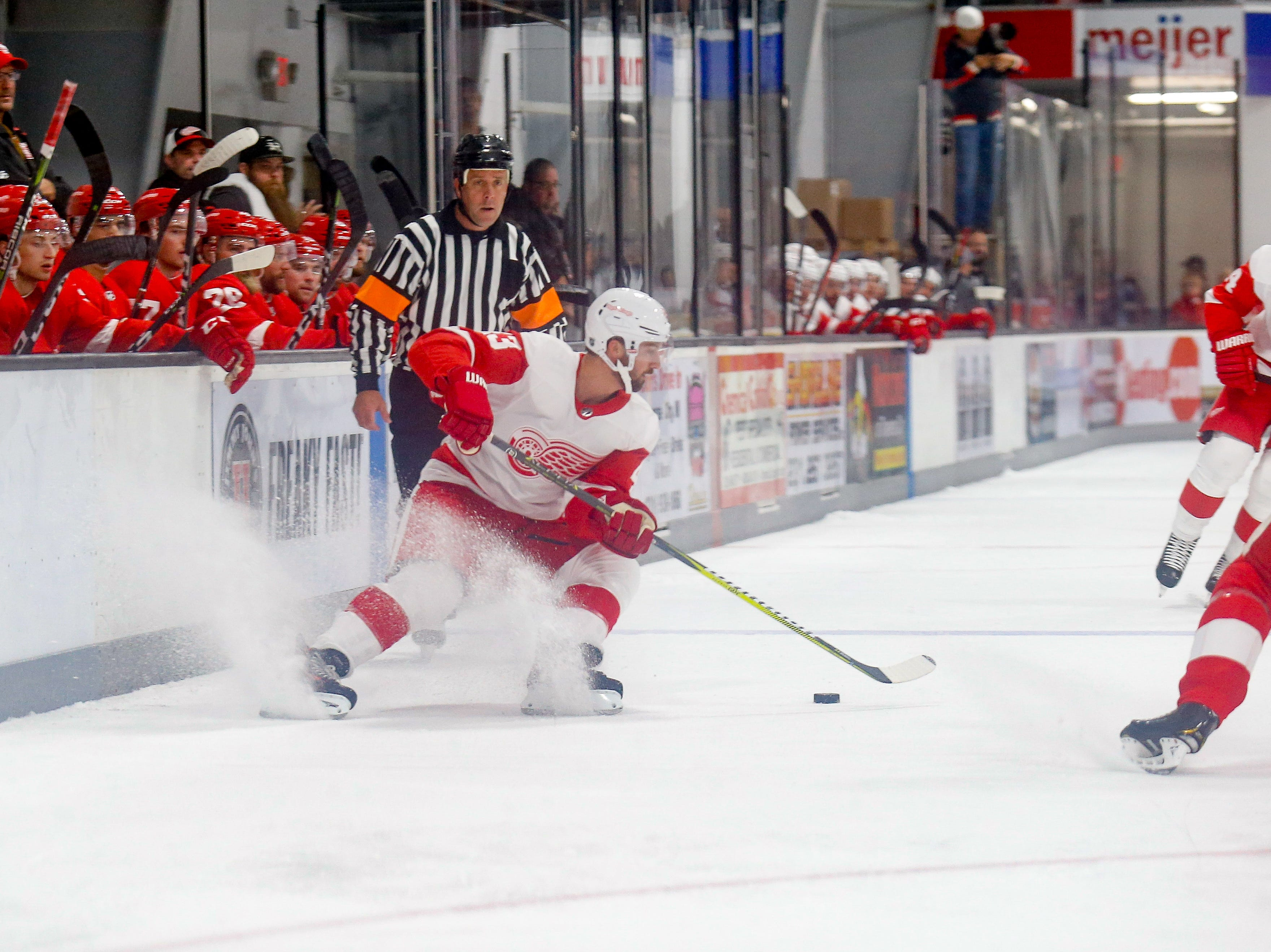 Darren Helm (43) stops and turns with the puck as Dennis Cholowski (21) defends against his advances.