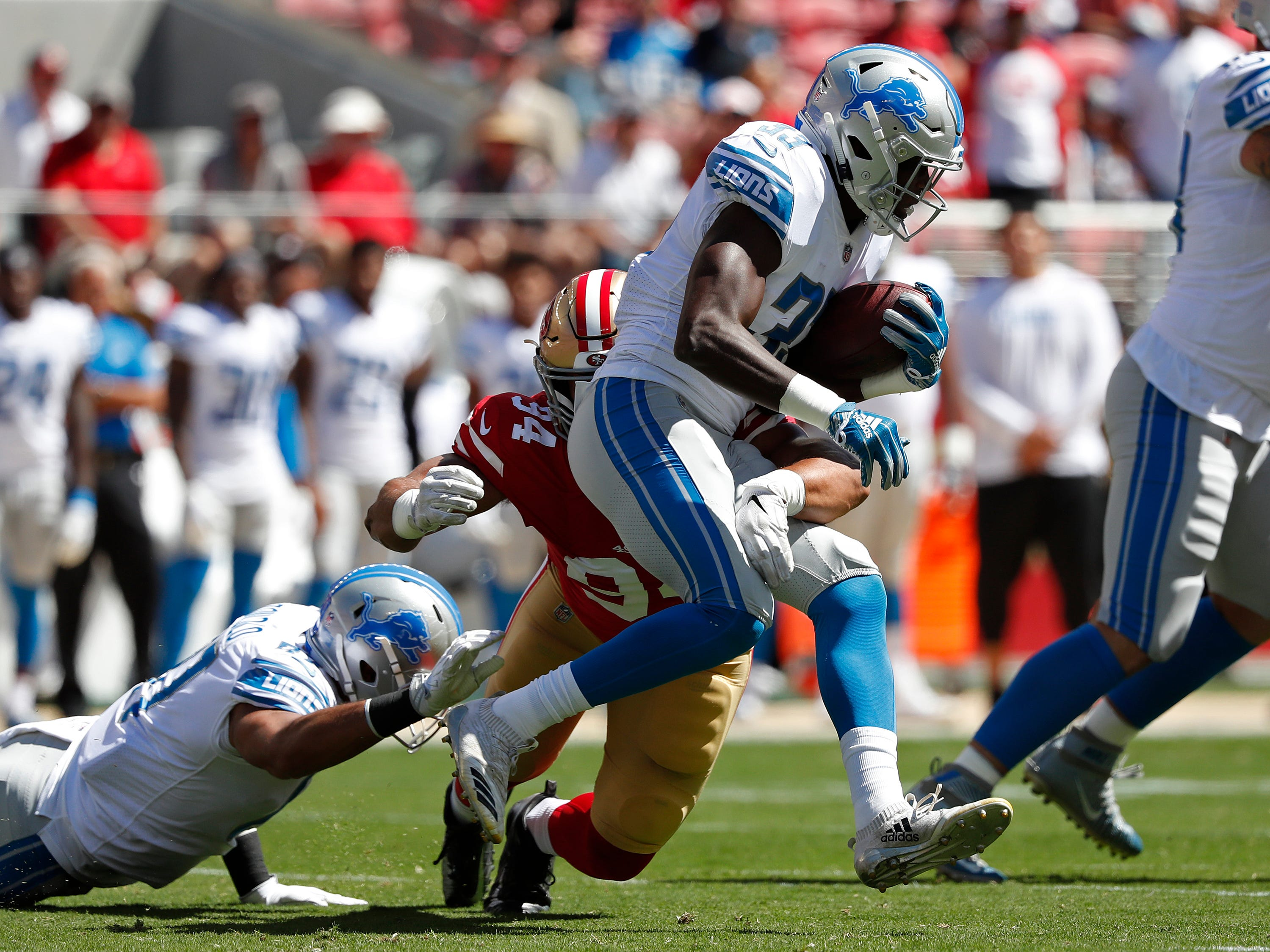 Detroit Lions running back Kerryon Johnson runs with the ball away from San Francisco 49ers defensive end Solomon Thomas during the first half.