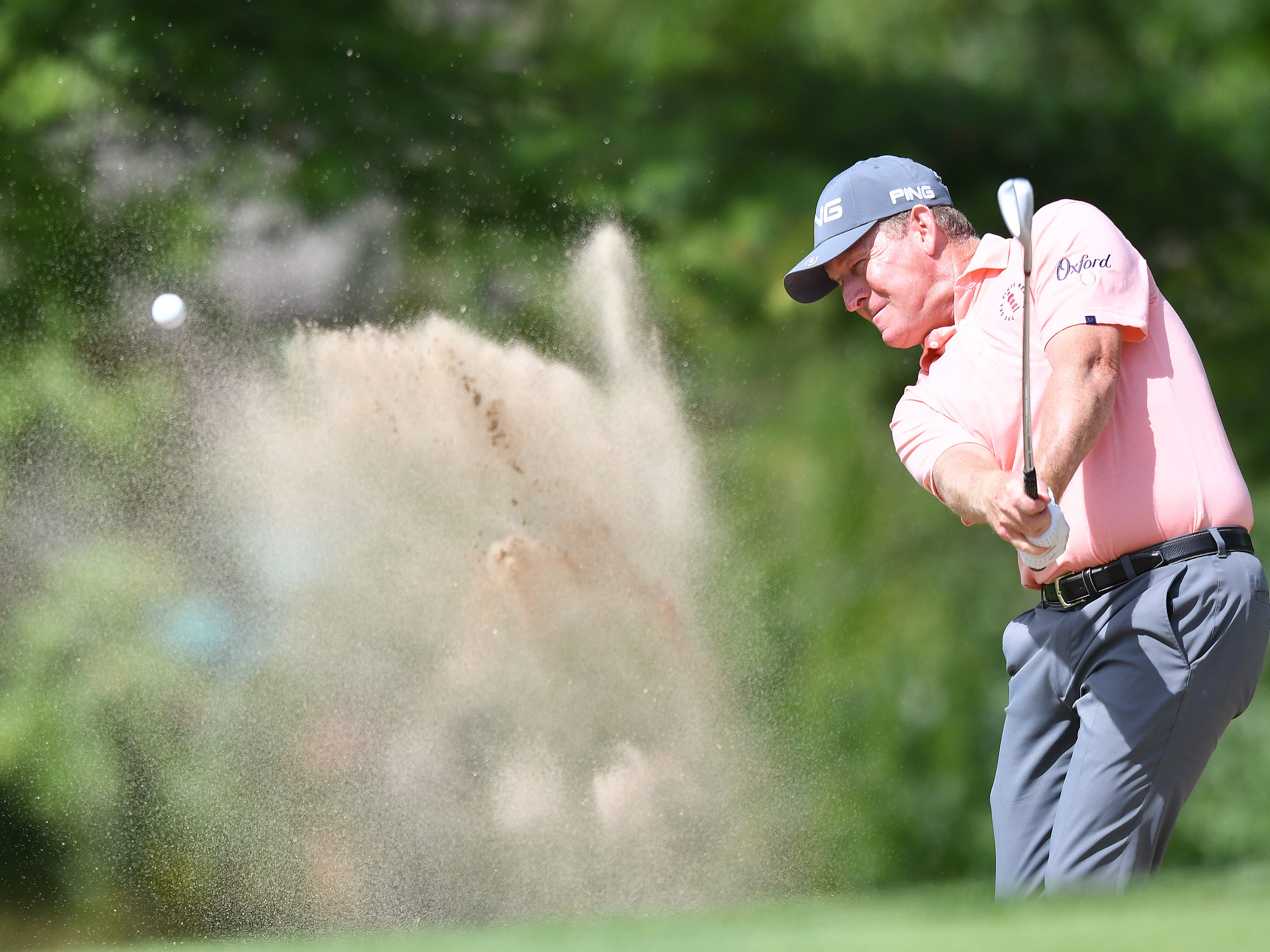 Jeff Maggert hits out of a bunker on the first hole.