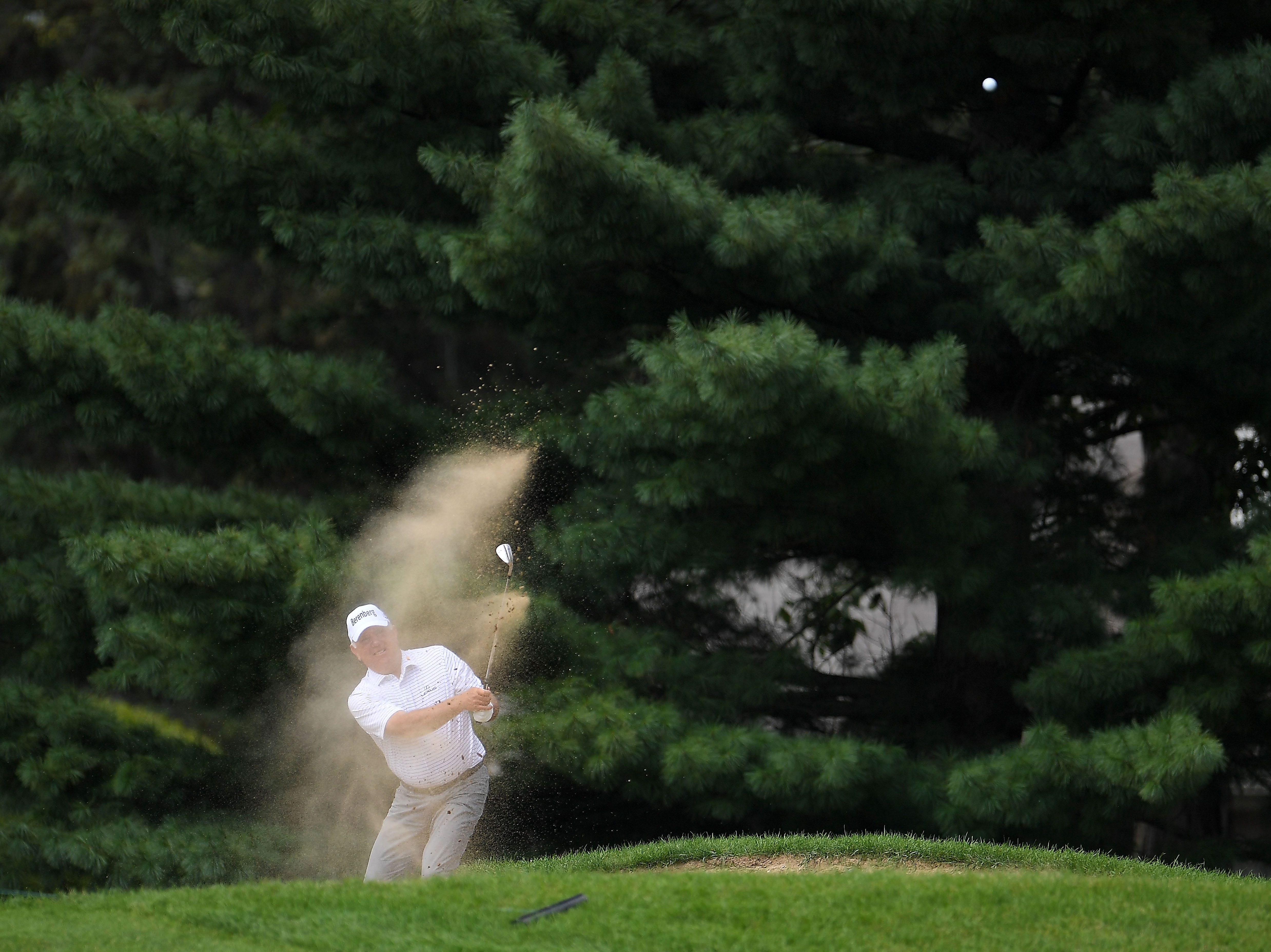 Mark O'Meara hits his third shot from a fairway bunker on the first hole.