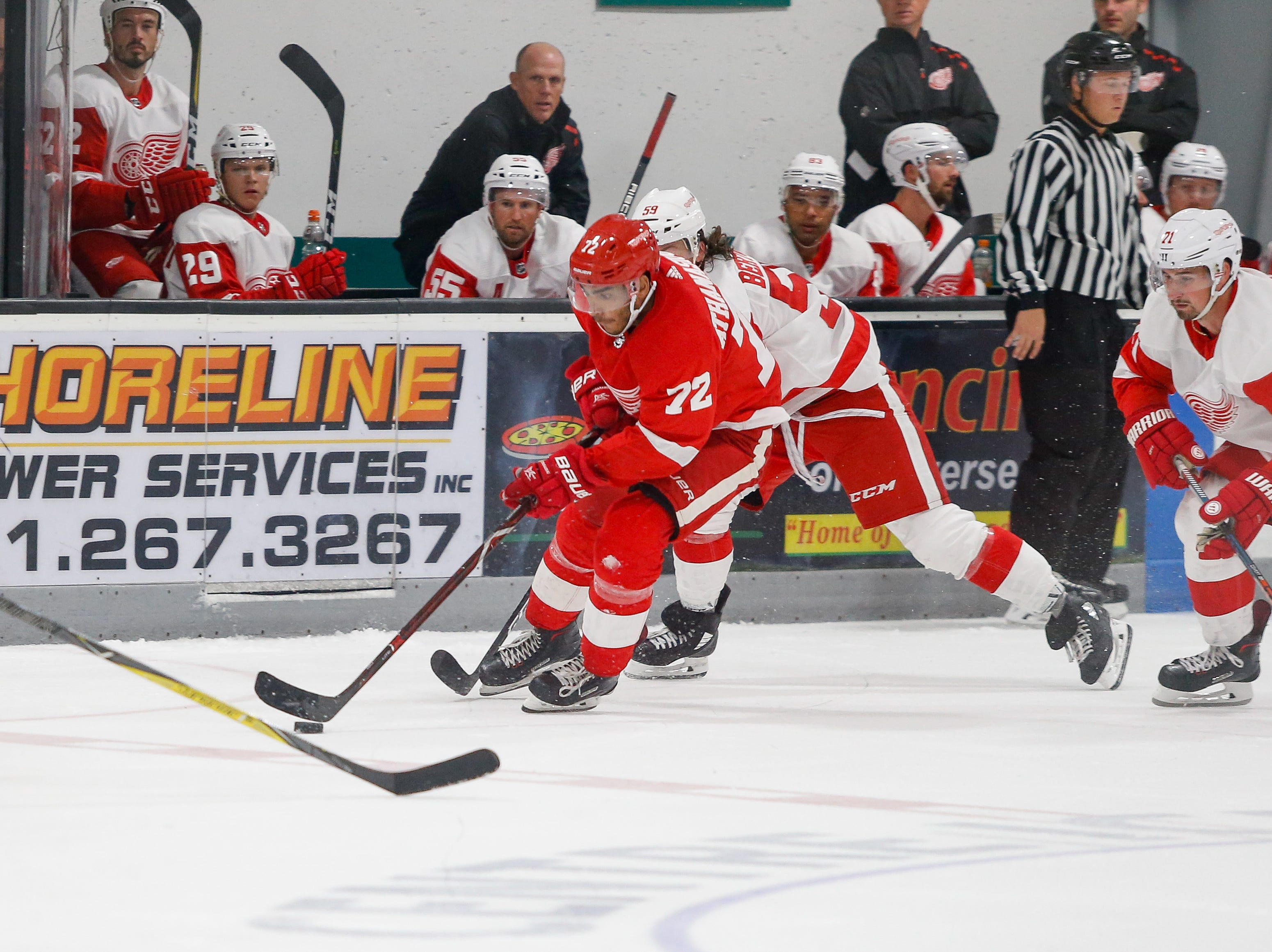 Andreas Athanasiou drives the puck across mid-ice as Team White's Tyler Bertuzzi (59) and Dylan Larkin (71) give chase.