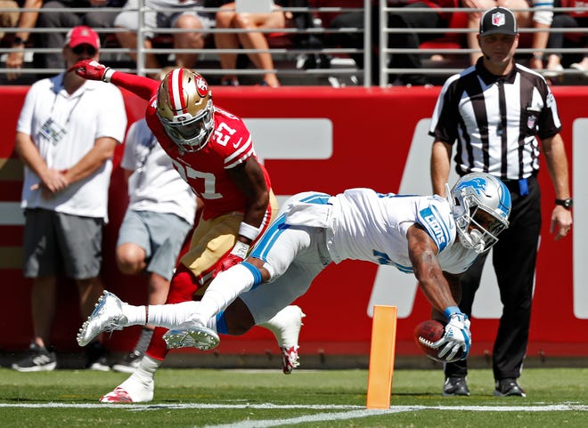 Detroit Lions wide receiver Kenny Golladay scores a touchdown as San Francisco 49ers defensive back Adrian Colbert looks on during the first half.