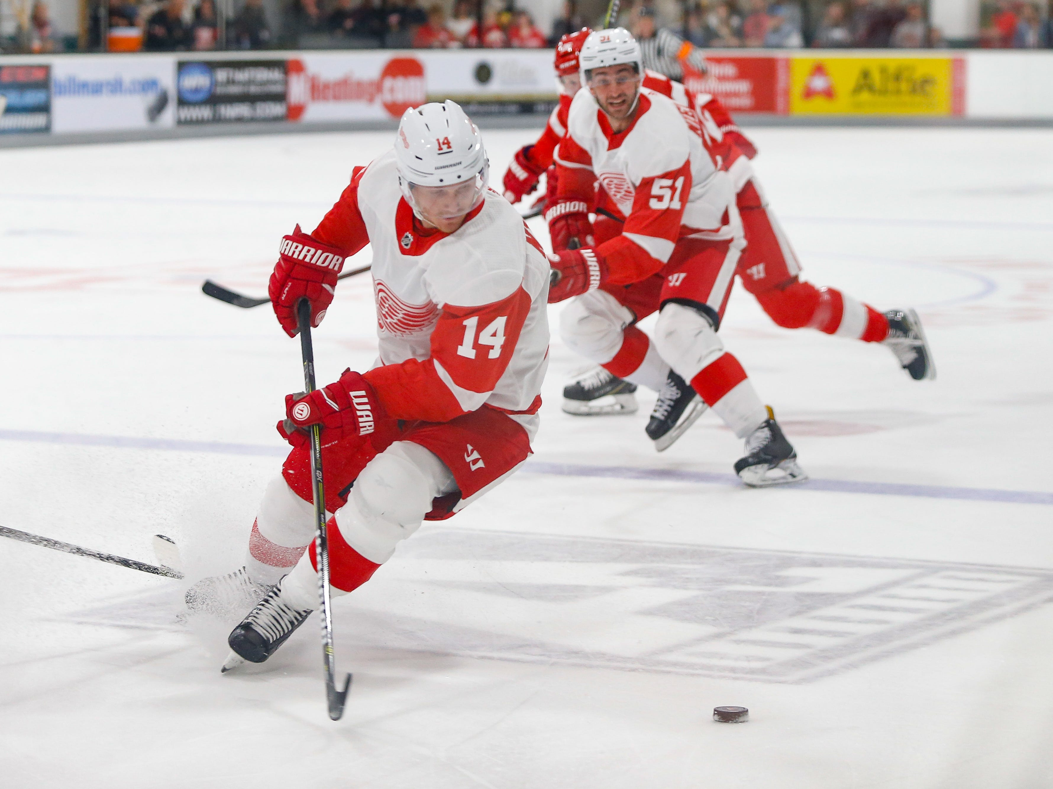 Forward Gustav Nyquist (14) turns to collect the puck as Frans Nielsen (51) looks on.