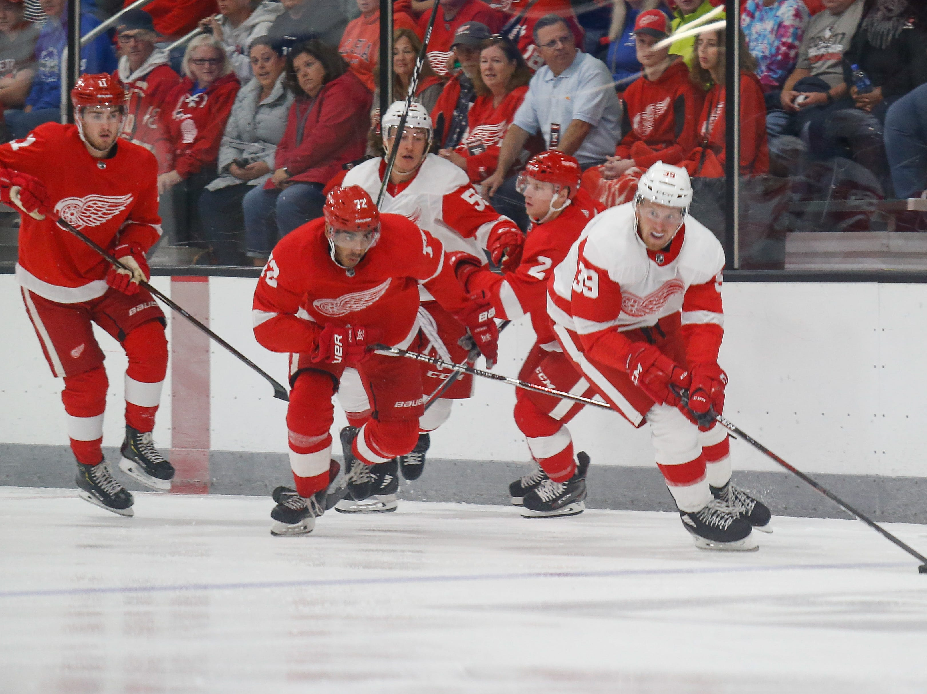 Anthony Mantha (39) carries the puck out of a scrum with Andreas Athanasiou (72) giving chase.