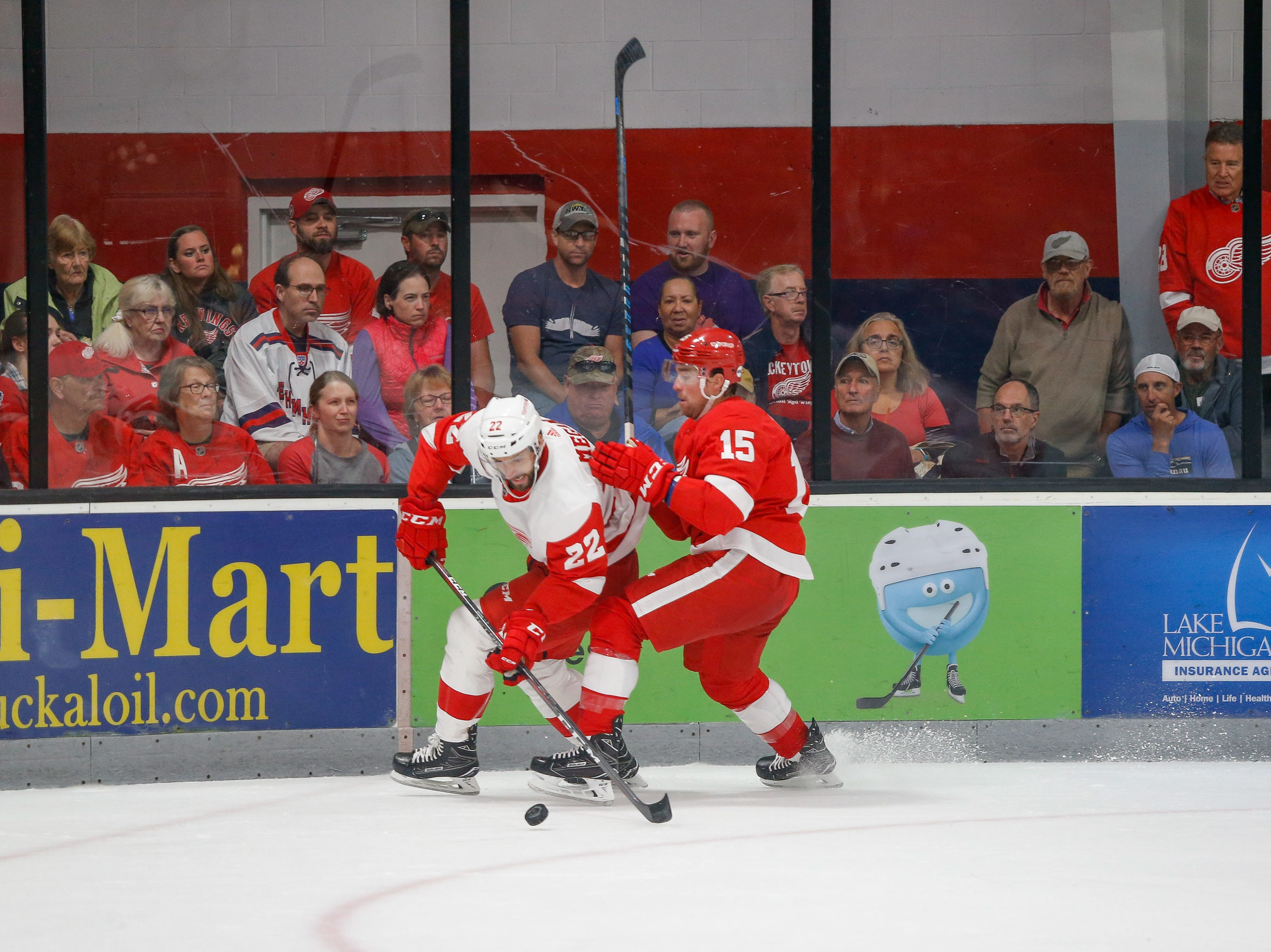 Wade Megan (22) and Chris Terry (15) go for a puck in the corner.