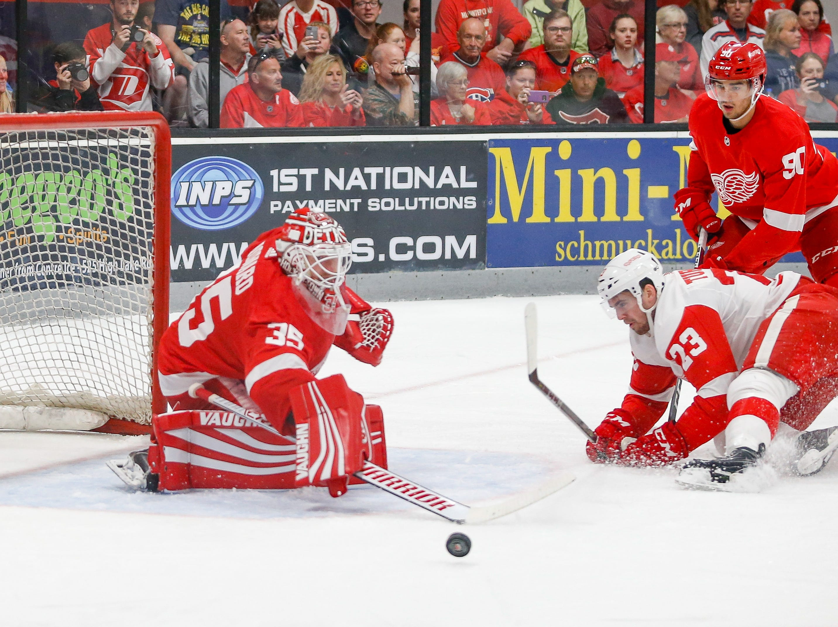 Goatender Jimmy Howard (35) brooms aside a shot by Dominic Turgeon (23), who was taken down on the play by Joe Veleno (90). Turgeon was awarded a penalty shot, but missed on it.
