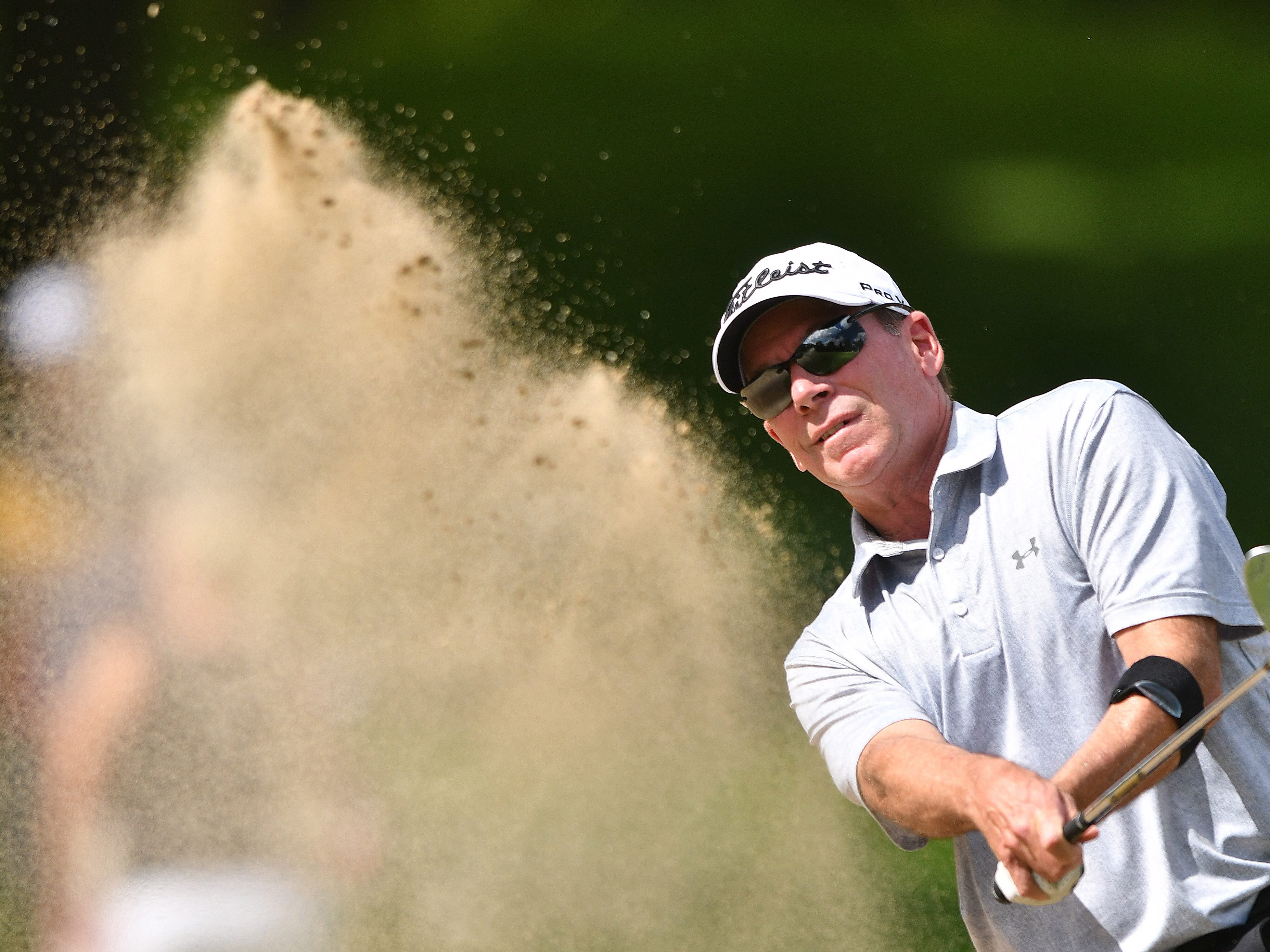 John Huston hits out of a bunker on the first hole at the Ally Challenge.