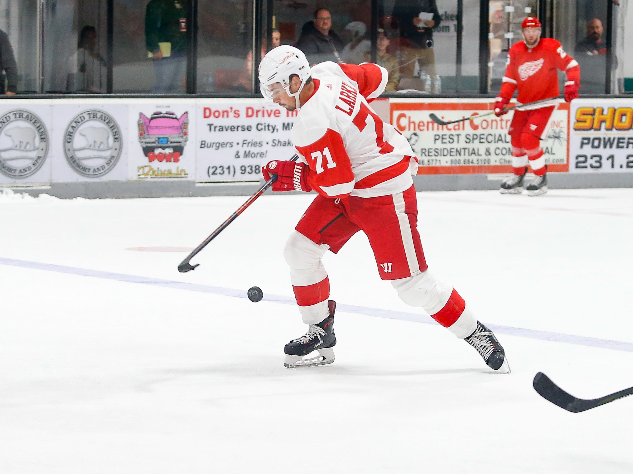 Dylan Larkin (71) looks to control the puck as he moves into Team Red's zone.