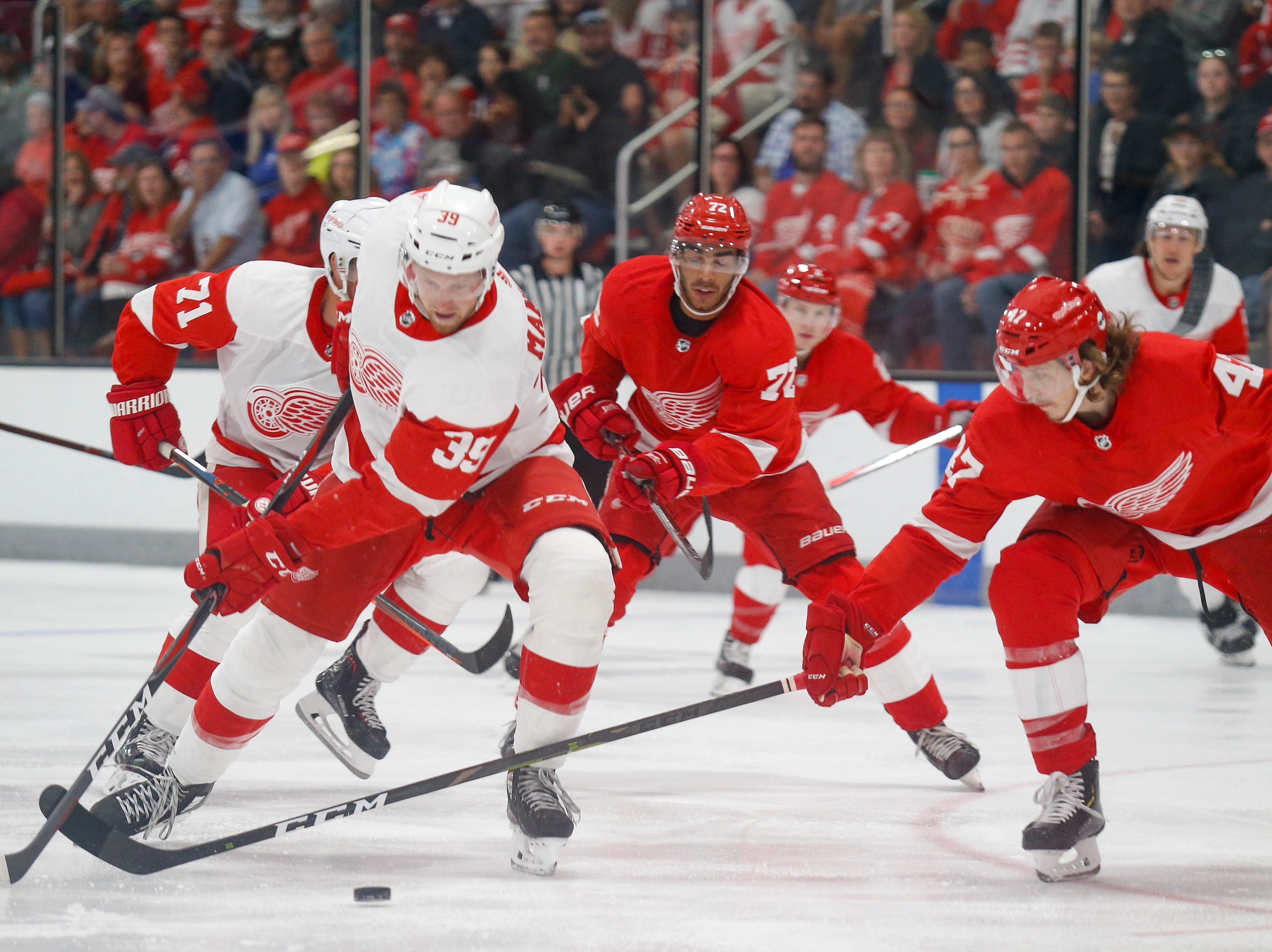 Anthony Mantha (39) tries to corral the puck with his backhand for a shot, but gets disrupted by Team Red defenseman Libor Sulak (47).