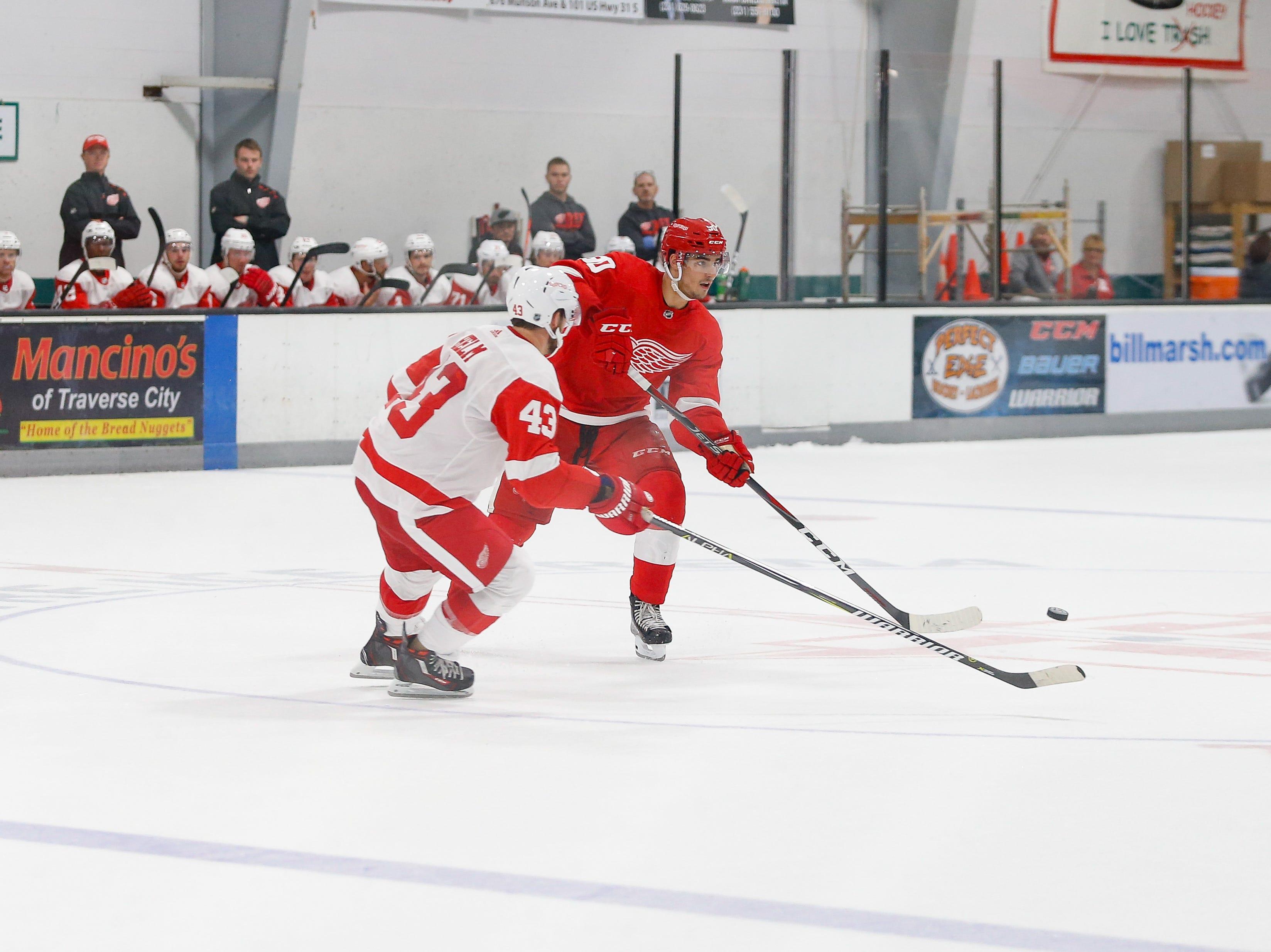 Joe Veleno sends a pass across ice as Darren Helm defends the white zone.