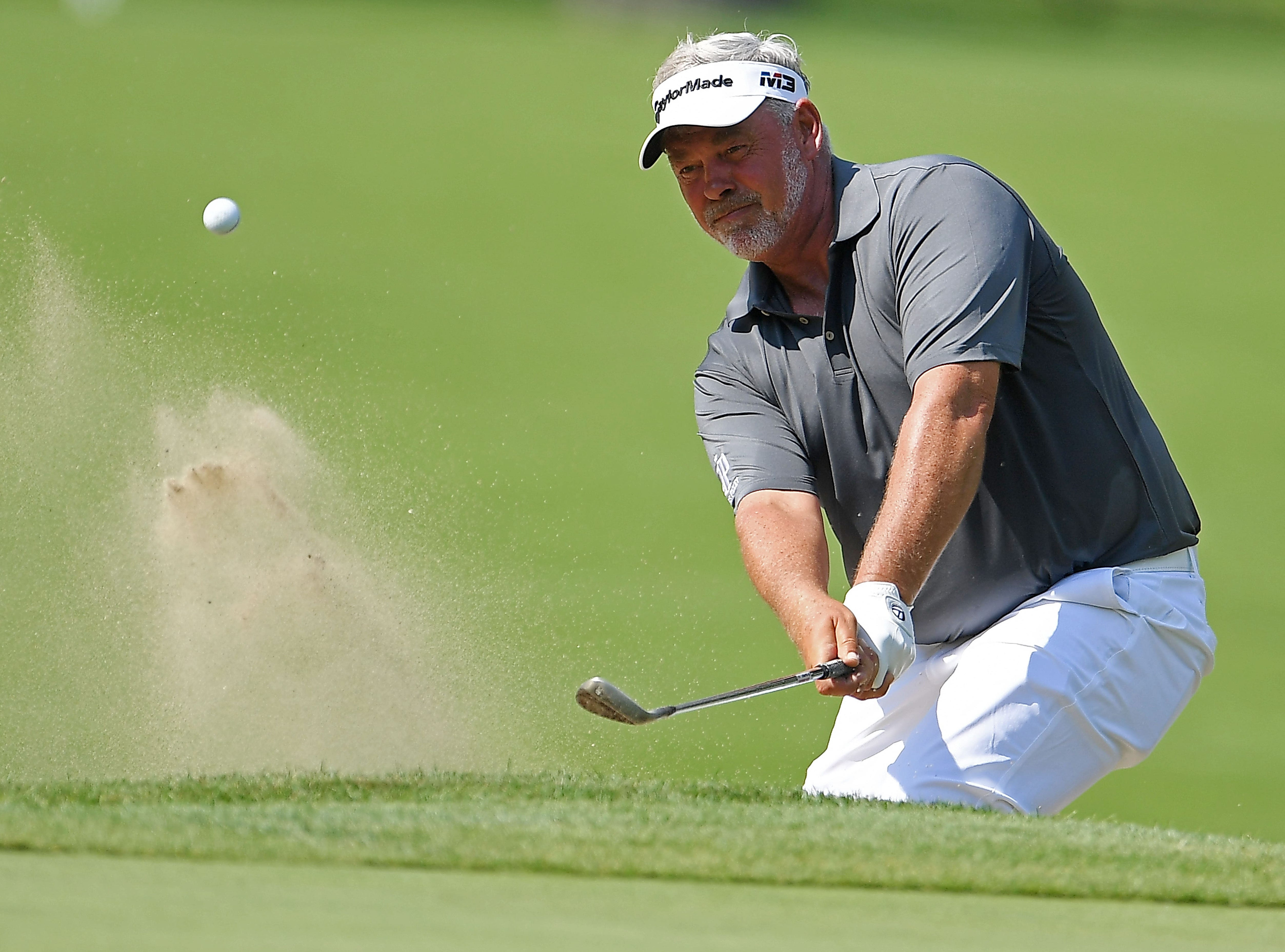 Darren Clarke hits from a green side bunker on the first hole.