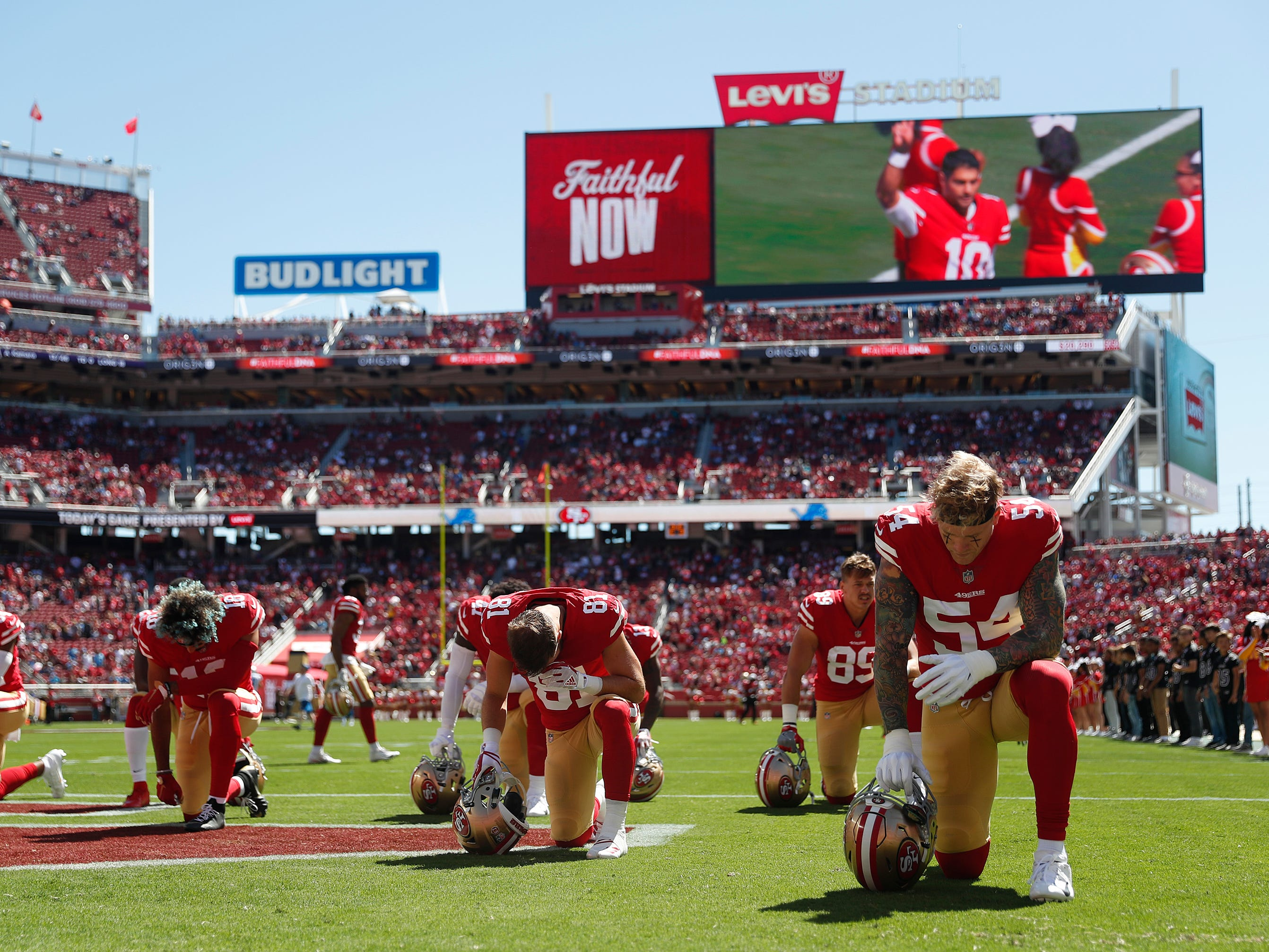 San Francisco 49ers kneel before the start of an NFL football game.