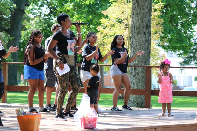 Lyn Darby, aunt of Jaylan Brock, who was shot and killed last year, leads a song and dance at his memorial on Saturday.