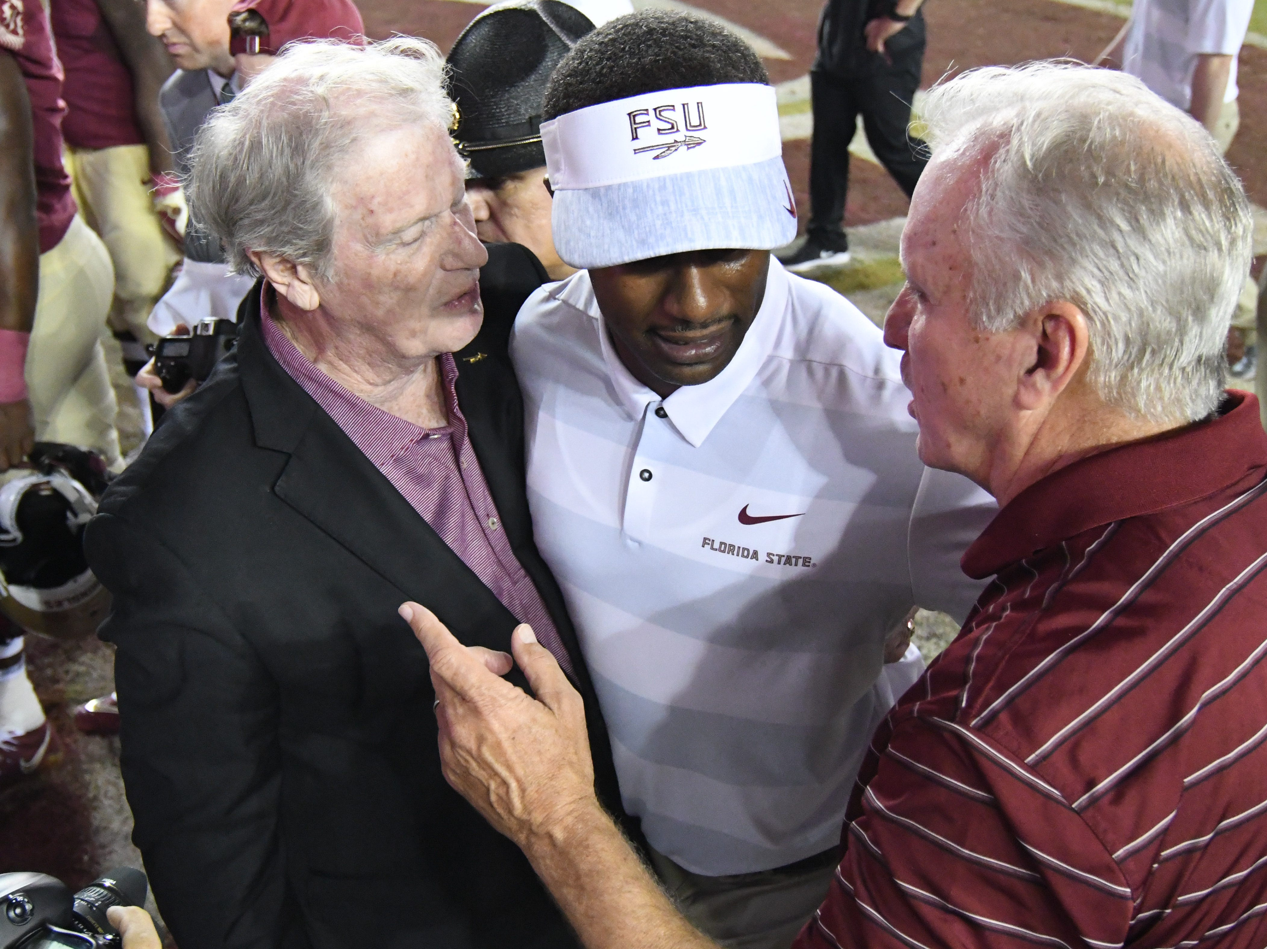 FSU head coach Willie Taggart talking to FSU President Thrasher after his first career win at Florida State.