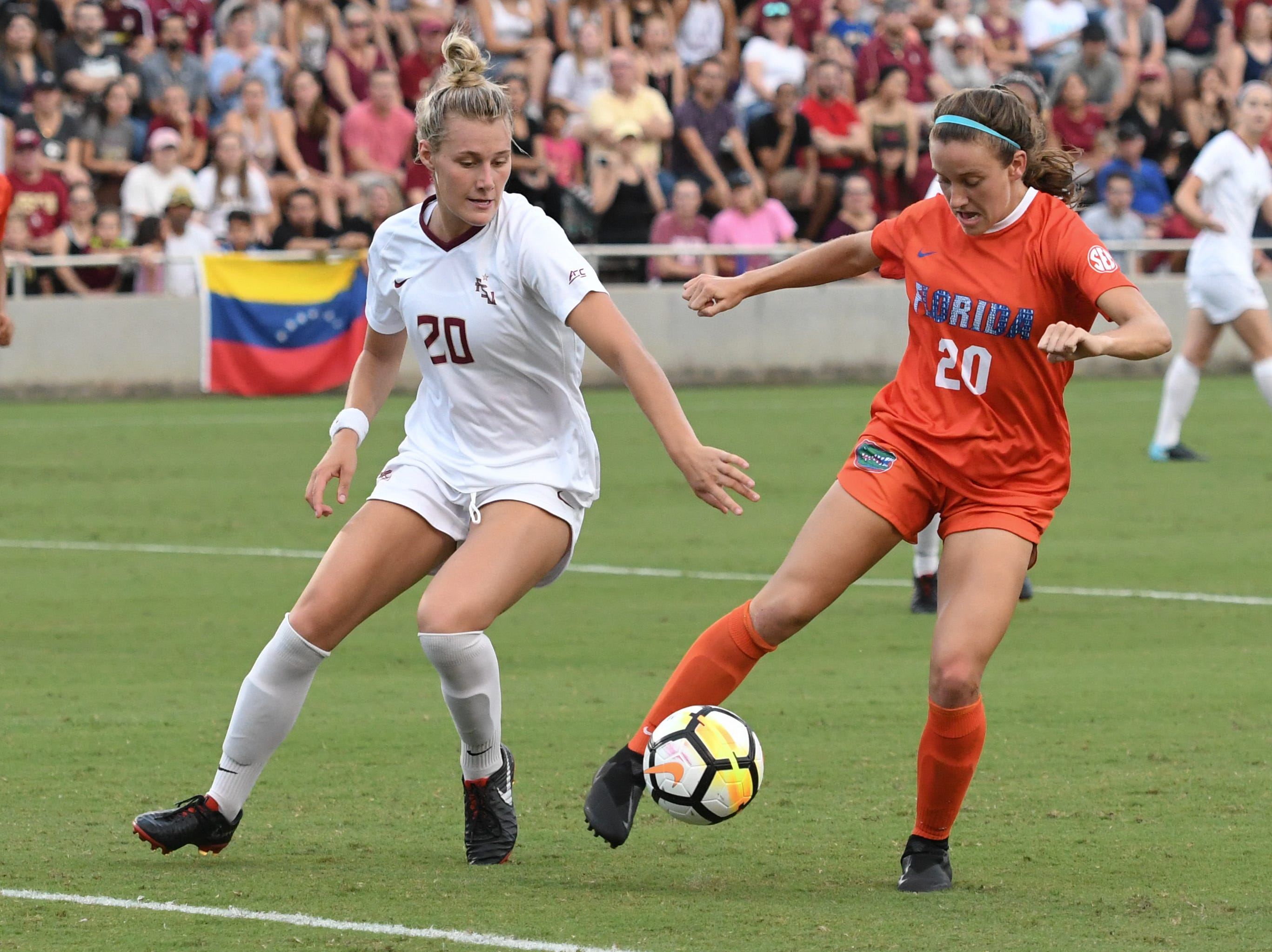 FSU redshirt sophomore forward Kristen McFarland (20) playing defense during the first half of FSU's game against Florida on friday night at the Seminole Soccer Complex.