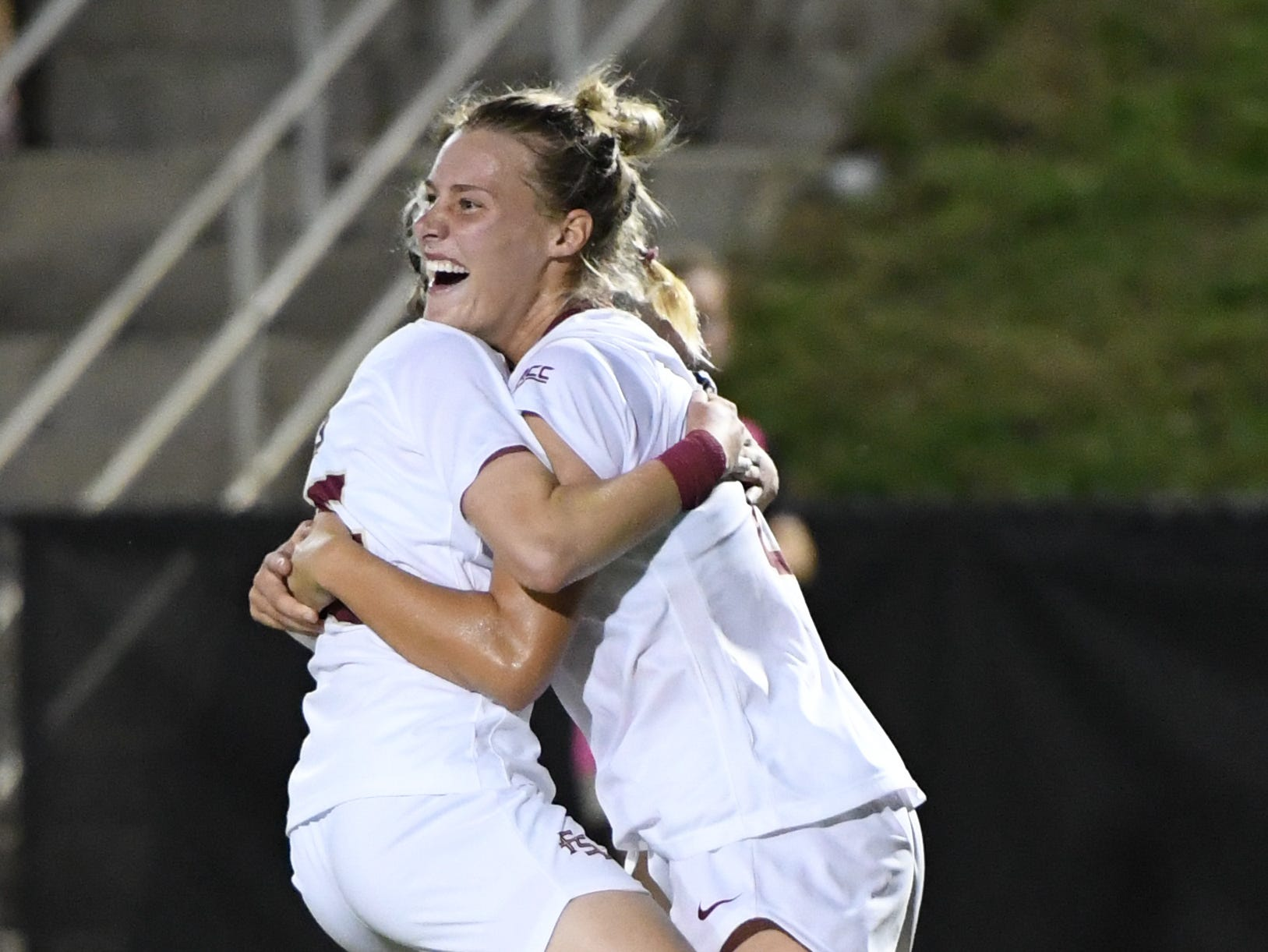 FSU redshirt sophomore forward Kristen McFarland (20) celebrating with her teammate after she scored FSU's winning goal during the second half of FSU's game against Florida on friday night at the Seminole Soccer Complex.