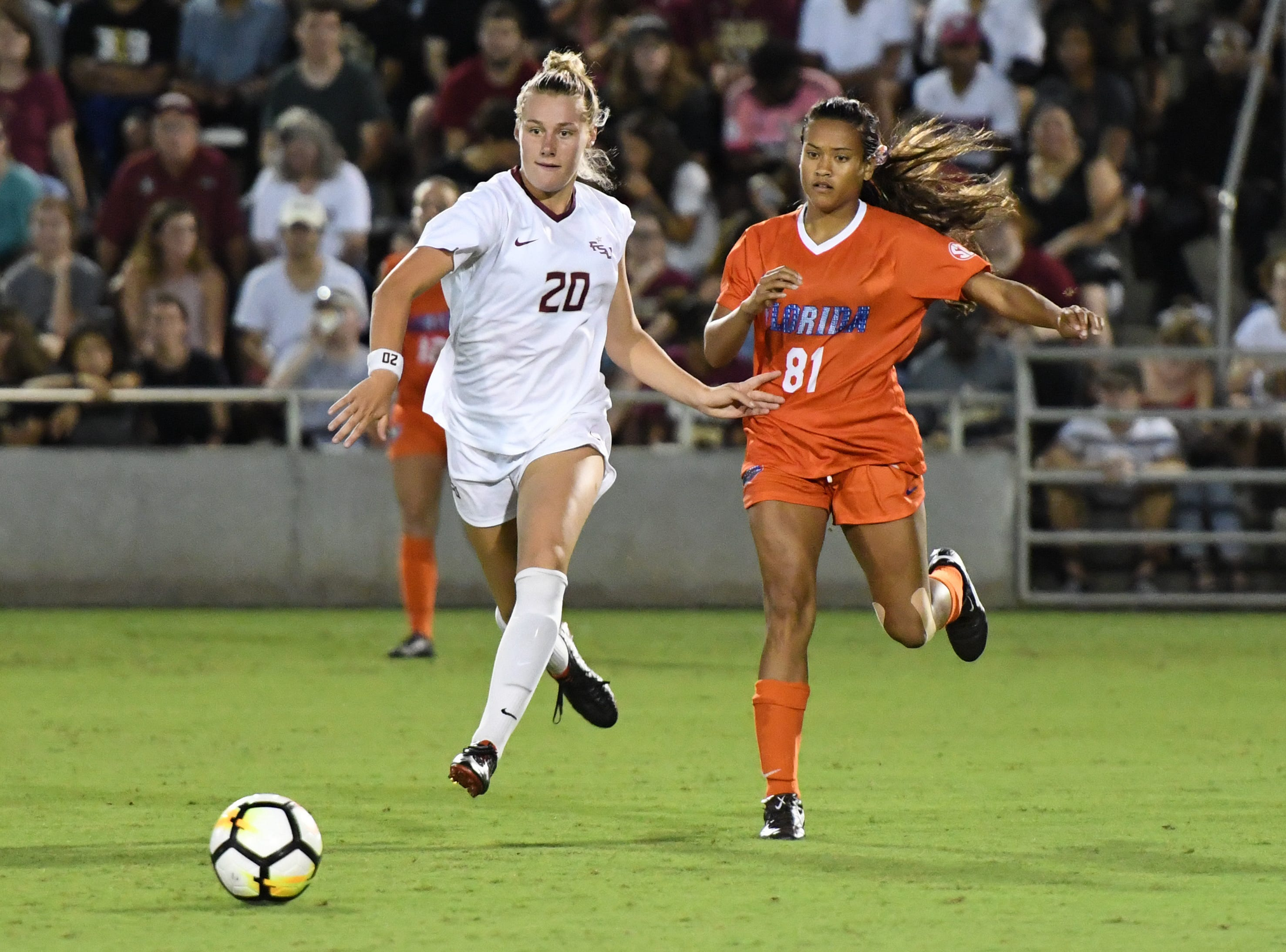 FSU redshirt sophomore forward Kristen McFarland (20) cuting through the Gator defense during the first half of FSU's game against Florida on friday night at the Seminole Soccer Complex.