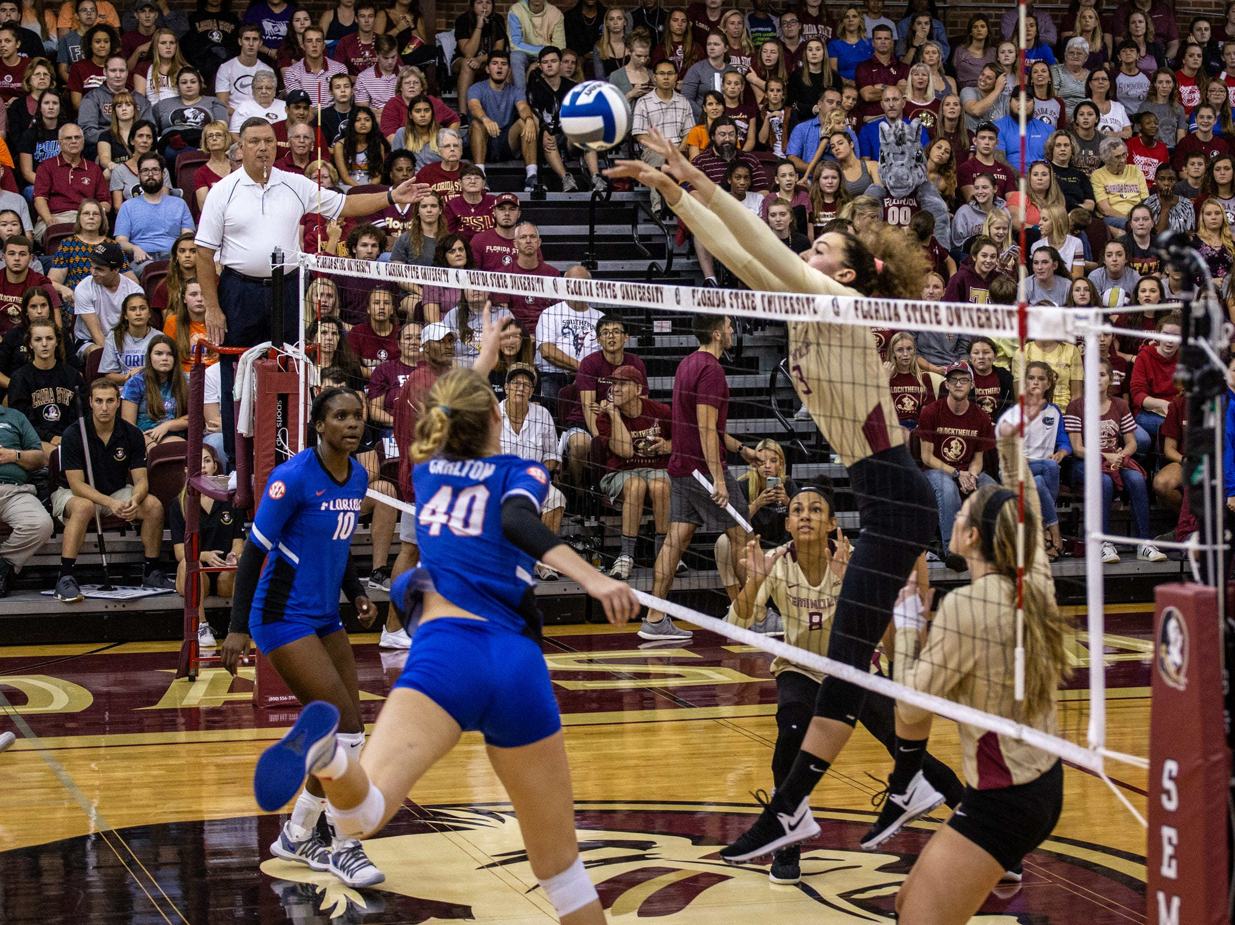 FSU outside hitter Morgan Chacon (3) blocks the ball sent over the net by UF's Holly Carlton (40) at Tully Gym.