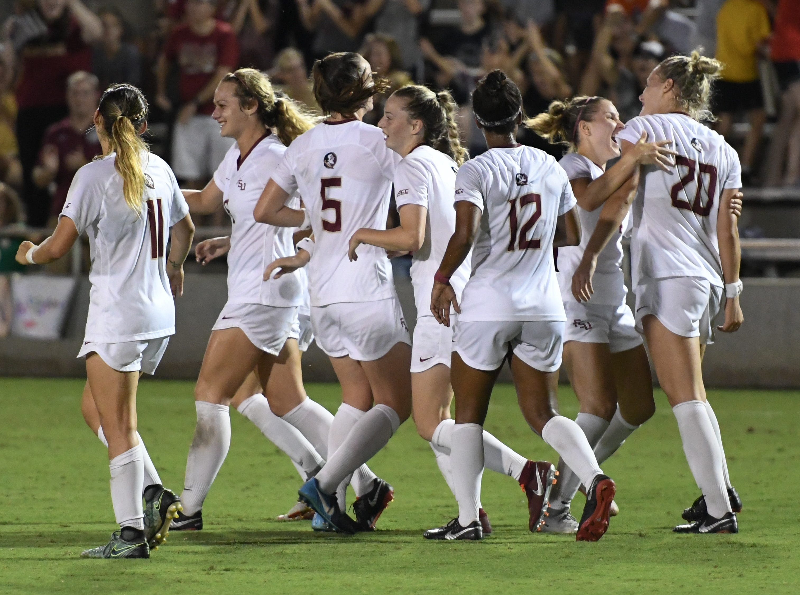 FSU redshirt sophomore forward Kristen McFarland (20) celebrating with her teammates after she scored FSU's winning goal during the second half of FSU's game against Florida on Friday night at the Seminole Soccer Complex.