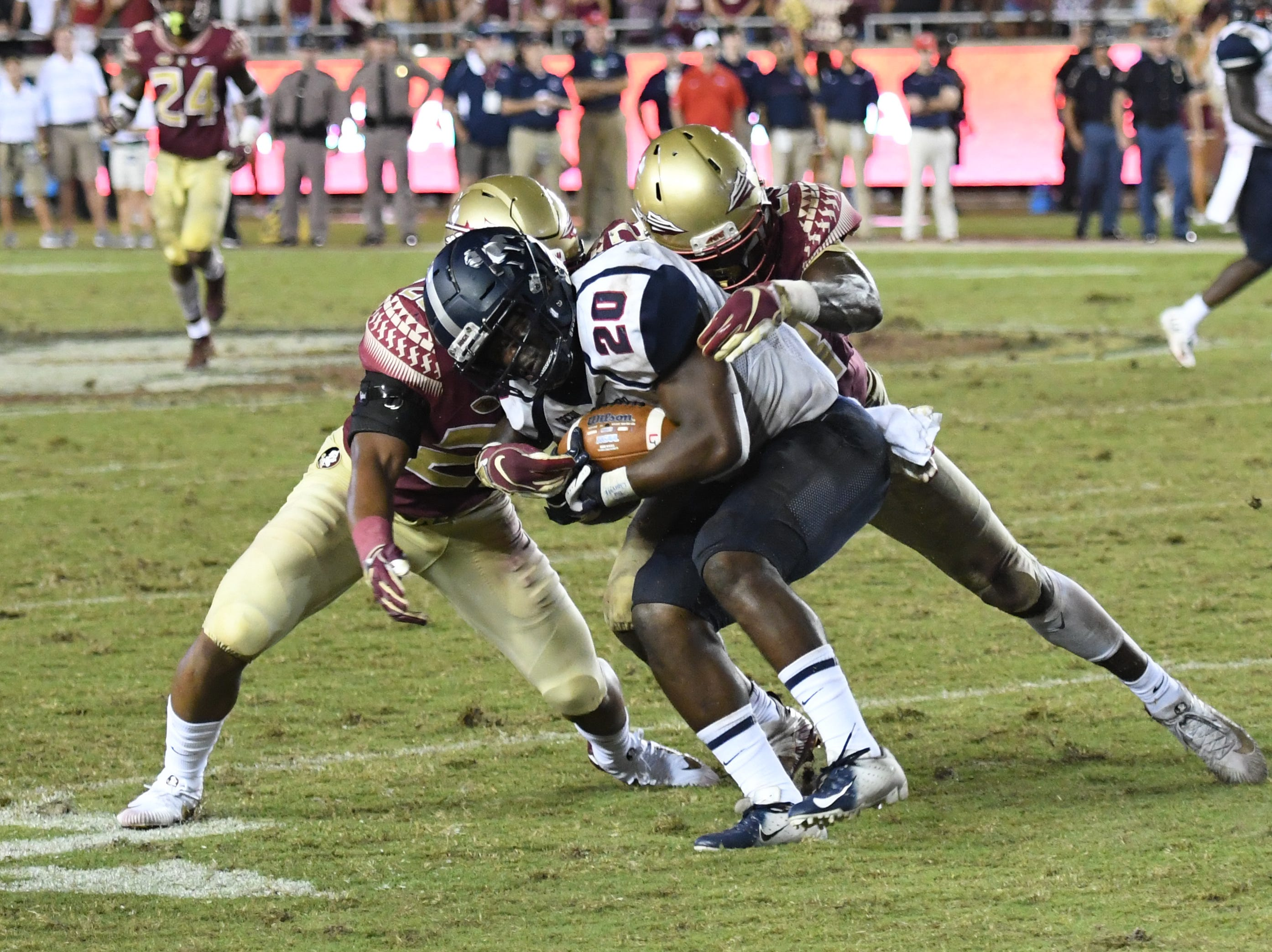 A couple of FSU defenders tackling a Samford running back during the fourth quarter of FSU's game against Samford on Saturday night at Doak Campbell Stadium.