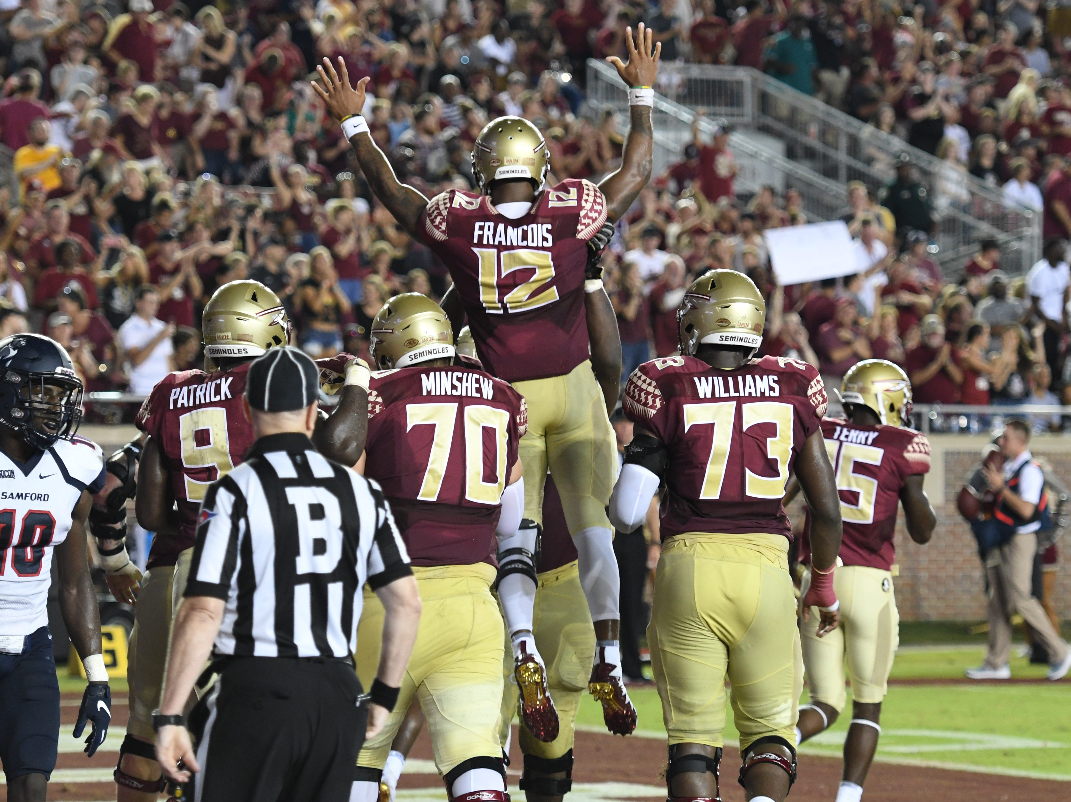 FSU redshirt junior Deondre Francois (12) celebrating his touchdown run with his teammates during the second quarter of FSU's matchup against Samford on Saturday night at Doak Campbell Stadium.