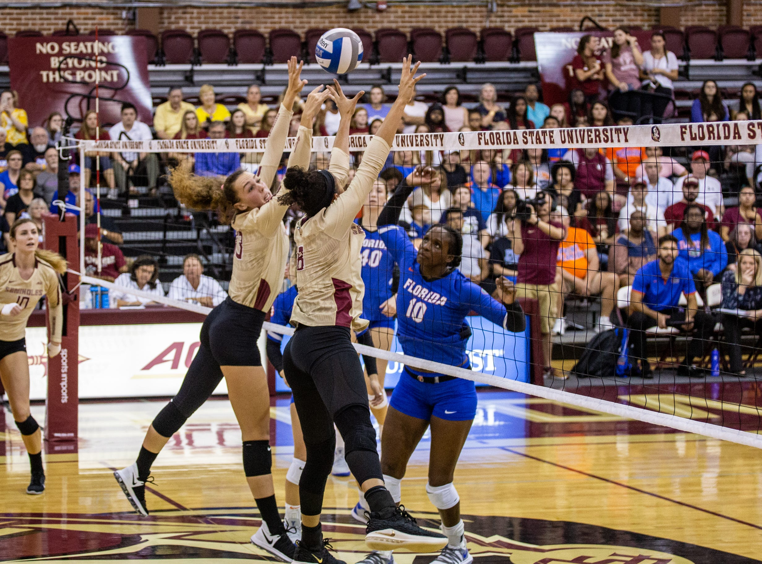 Morgan Chacon (3) and Tiana Jackson (8), block a spike sent over the net by UF's Taelor Kellum (10) during the first set against Florida at Tully Gymnasium on Wednesday.