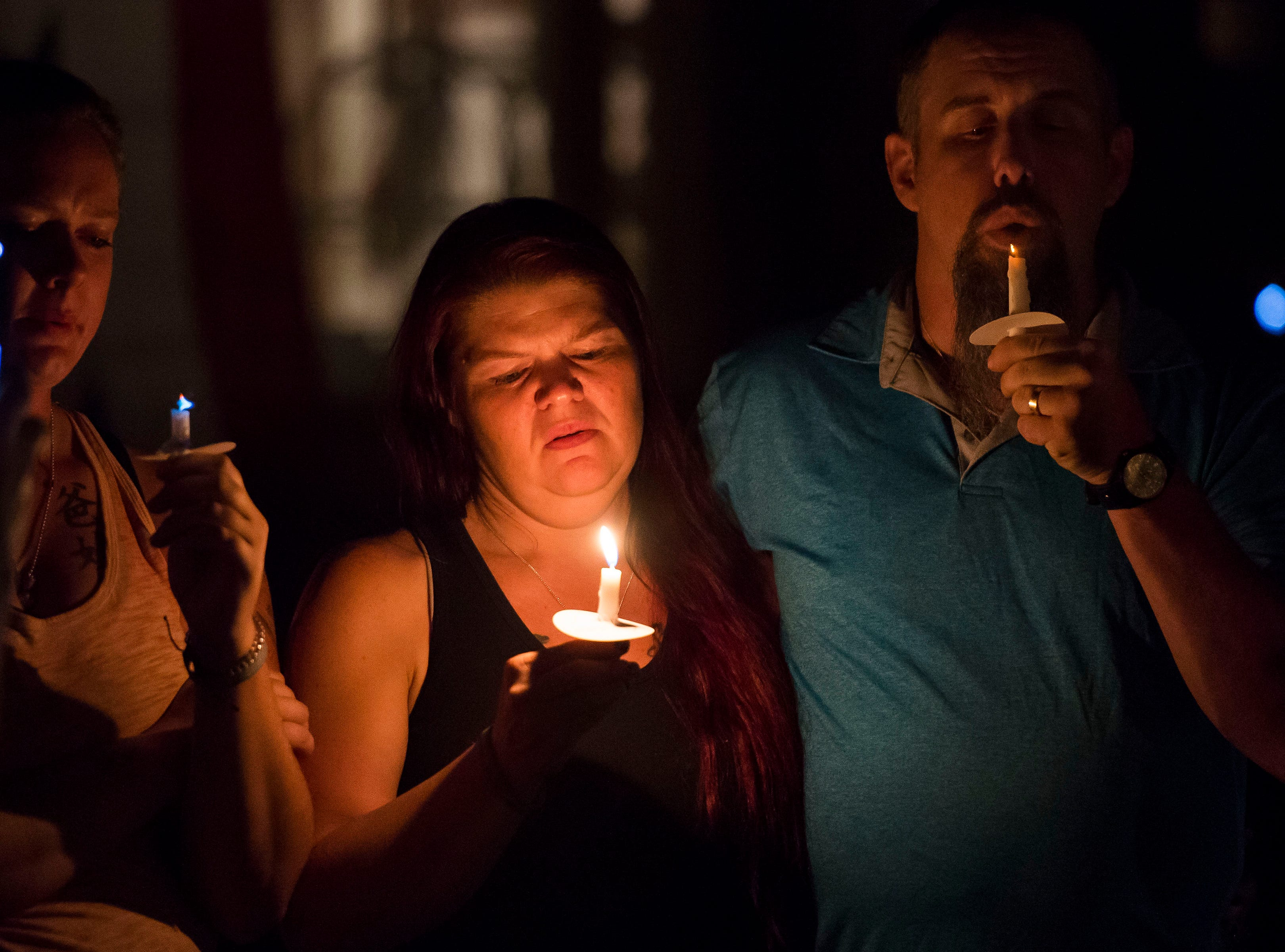 Penny Whaley, center, pauses before blowing out a candle at the end of a vigil for her son Aric Whaley, a 17 year old who was fatally shot at his home early Tuesday morning, Sept. 4, as seen on Saturday, Sept. 15, 2018, in Loveland, Colo. Gabriel Jesus Romero Ventura, 18, was arrested by Loveland police less than a mile from the residence on suspicion of manslaughter, first-degree assault and prohibited use of a weapon.