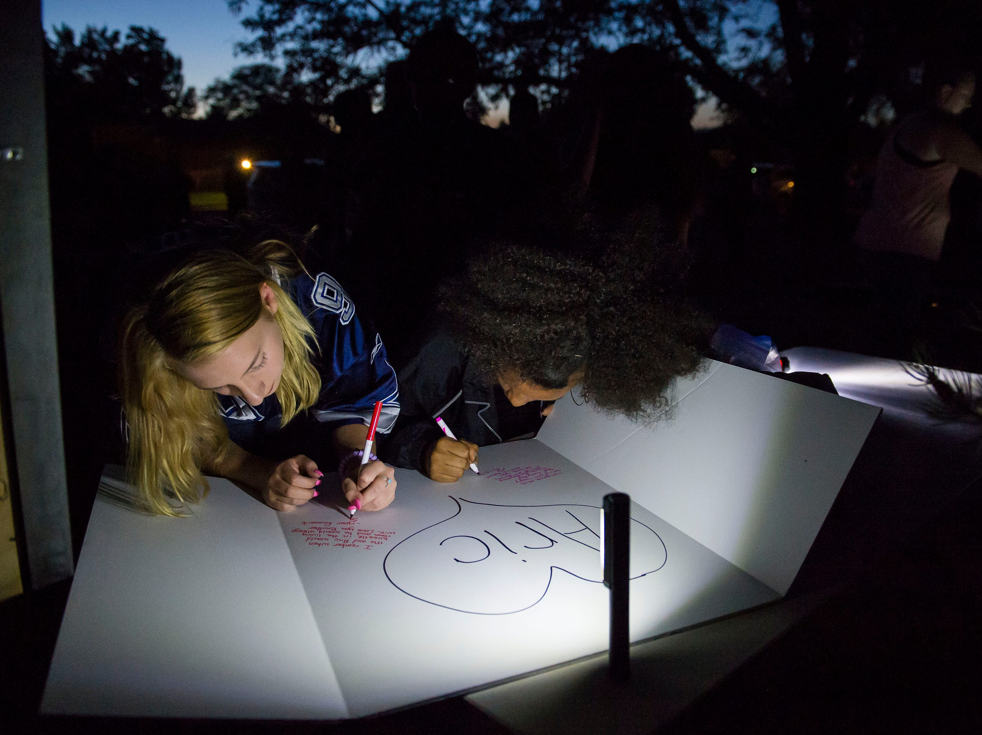 Family and friends write messages on a poster board while other mourners gather for a vigil in front of the home of Aric Whaley, a 17 year old who was fatally shot at the home early Tuesday morning, Sept. 4, as seen on Saturday, Sept. 15, 2018, in Loveland, Colo. Gabriel Jesus Romero Ventura, 18, was arrested by Loveland police less than a mile from the residence on suspicion of manslaughter, first-degree assault and prohibited use of a weapon.