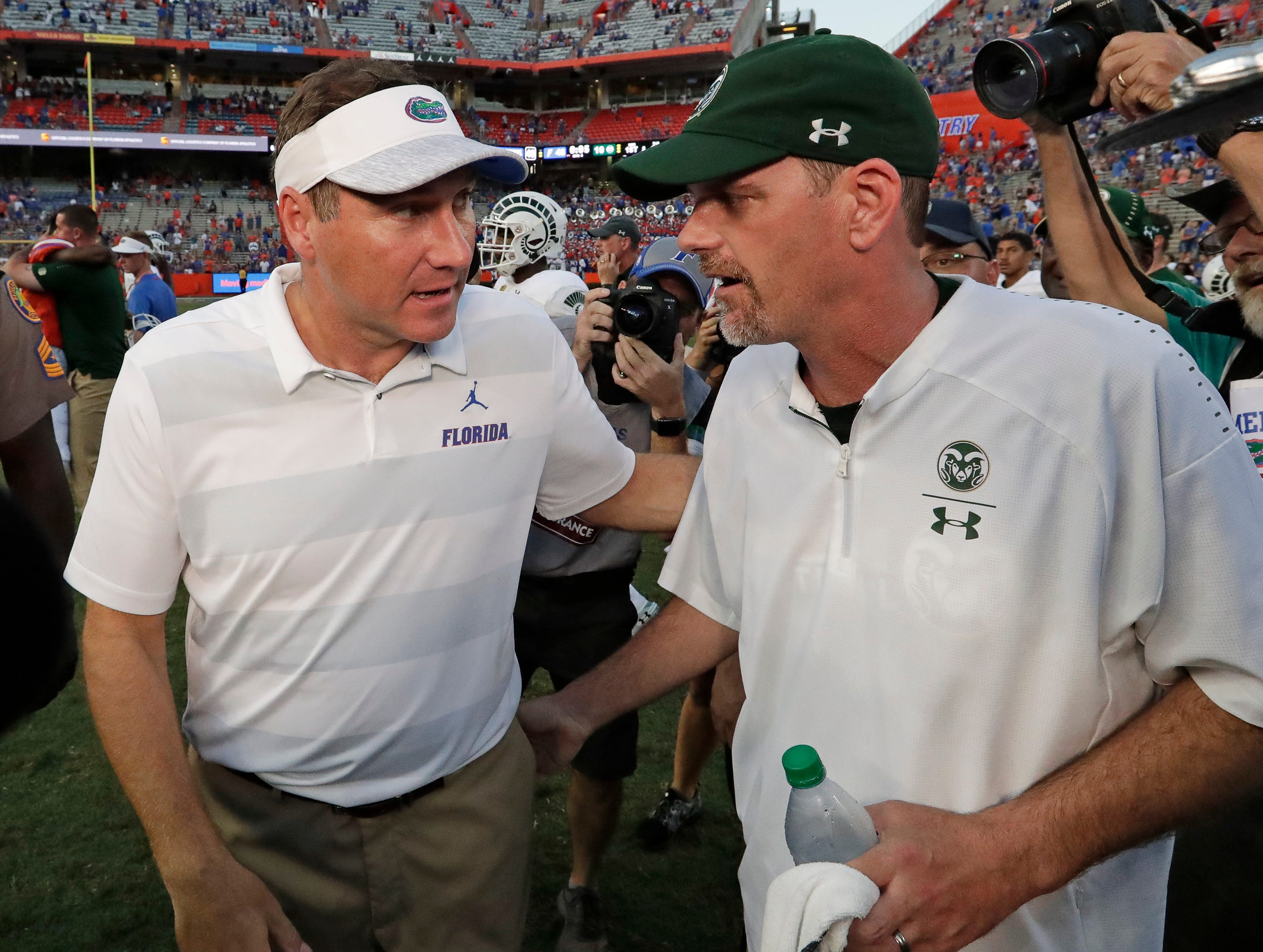 Florida head coach Dan Mullen, left, greets Colorado State head coach Mike Bobo after an NCAA college football game, Saturday, Sept. 15, 2018, in Gainesville, Fla. (AP Photo/John Raoux)