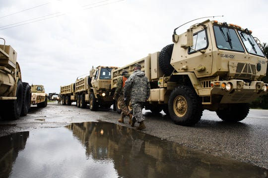 South Carolina Army National Guard trucks sit along U.S. 501 South just outside of Conway to deliver sand to other units stationed along the Waccamaw River due to Tropical Depression Florence on Sunday, Sept. 16, 2018.