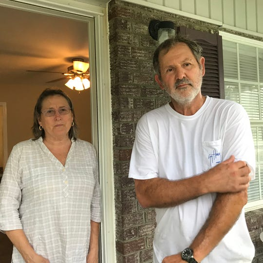 Dale Gordon, left, and her husband Mike, take a break from loading furniture into a trailer at their home in Nichols.