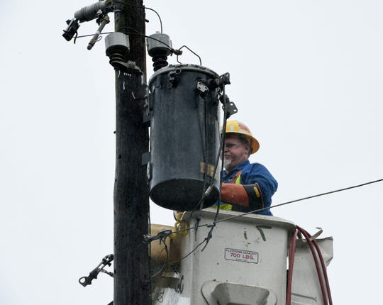In this file photo, a utility worker removes a damaged transformer after a large oak tree on Crescent Avenue in Greenville, South Carolina, had fallen across power lines on Sept. 16, 2018.