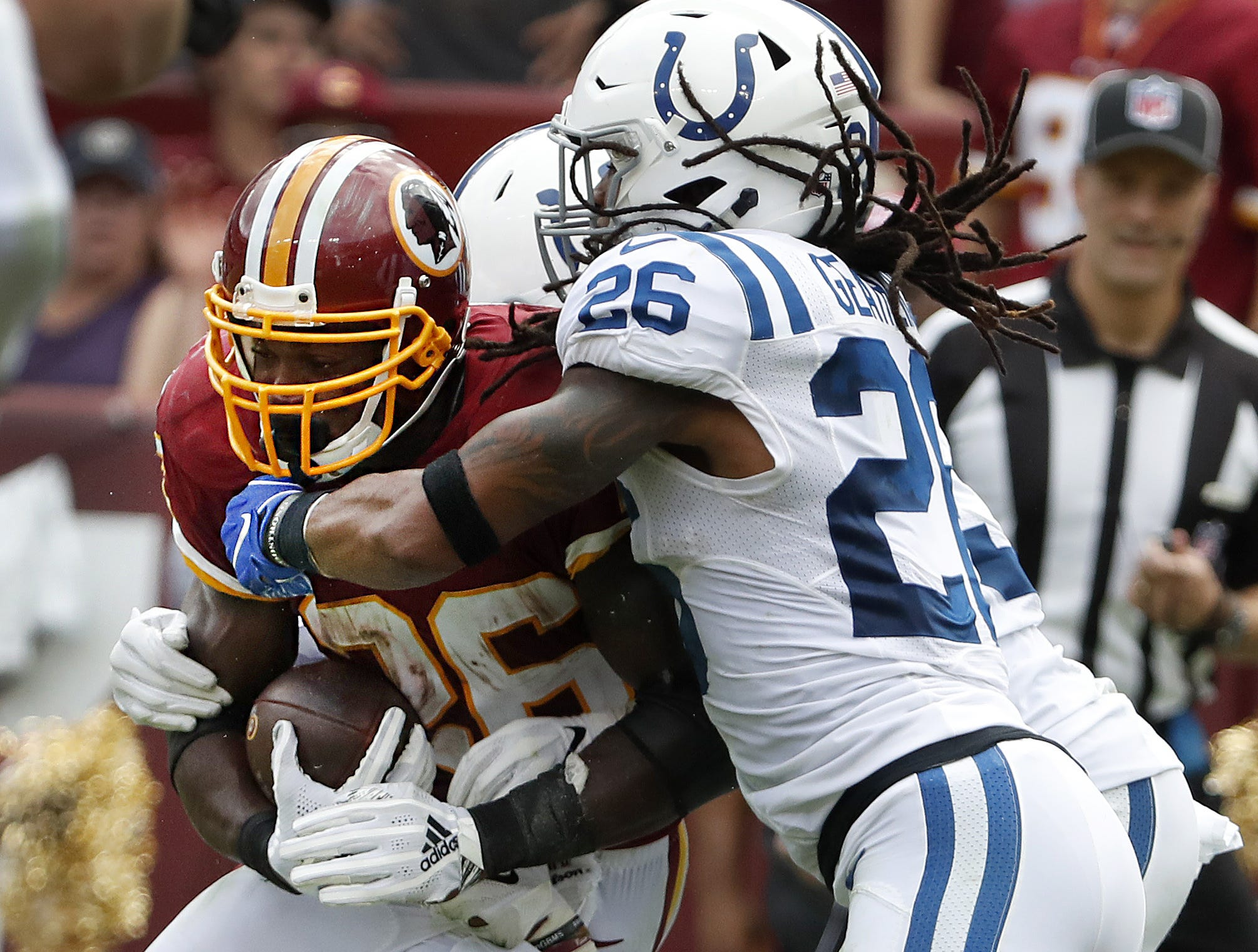 Indianapolis Colts defensive back Clayton Geathers (26) hits Washington Redskins running back Adrian Peterson (26) in the second half of their game at FedEx Field in Landover MD. on Sunday, Sept. 16, 2018.
