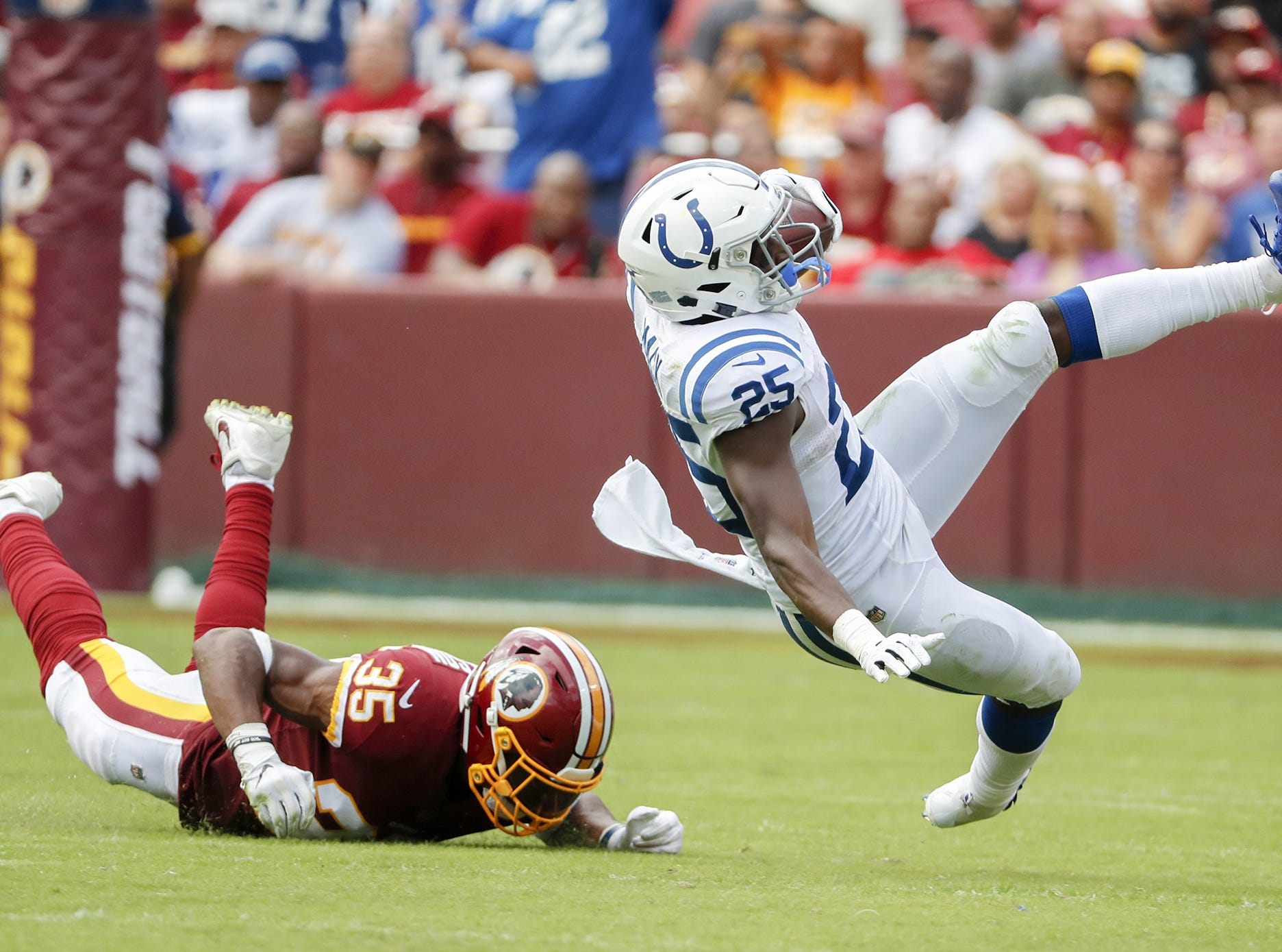 Indianapolis Colts running back Marlon Mack (25) looses his footing as he works to elude the tackling efforts of Washington Redskins defensive back Montae Nicholson (35) during second half action. The Indianapolis Colts play the Washington Redskins at FedEx Field in Landover, MD., Sunday, Sept. 16, 2018. Colts won the game 21-9.